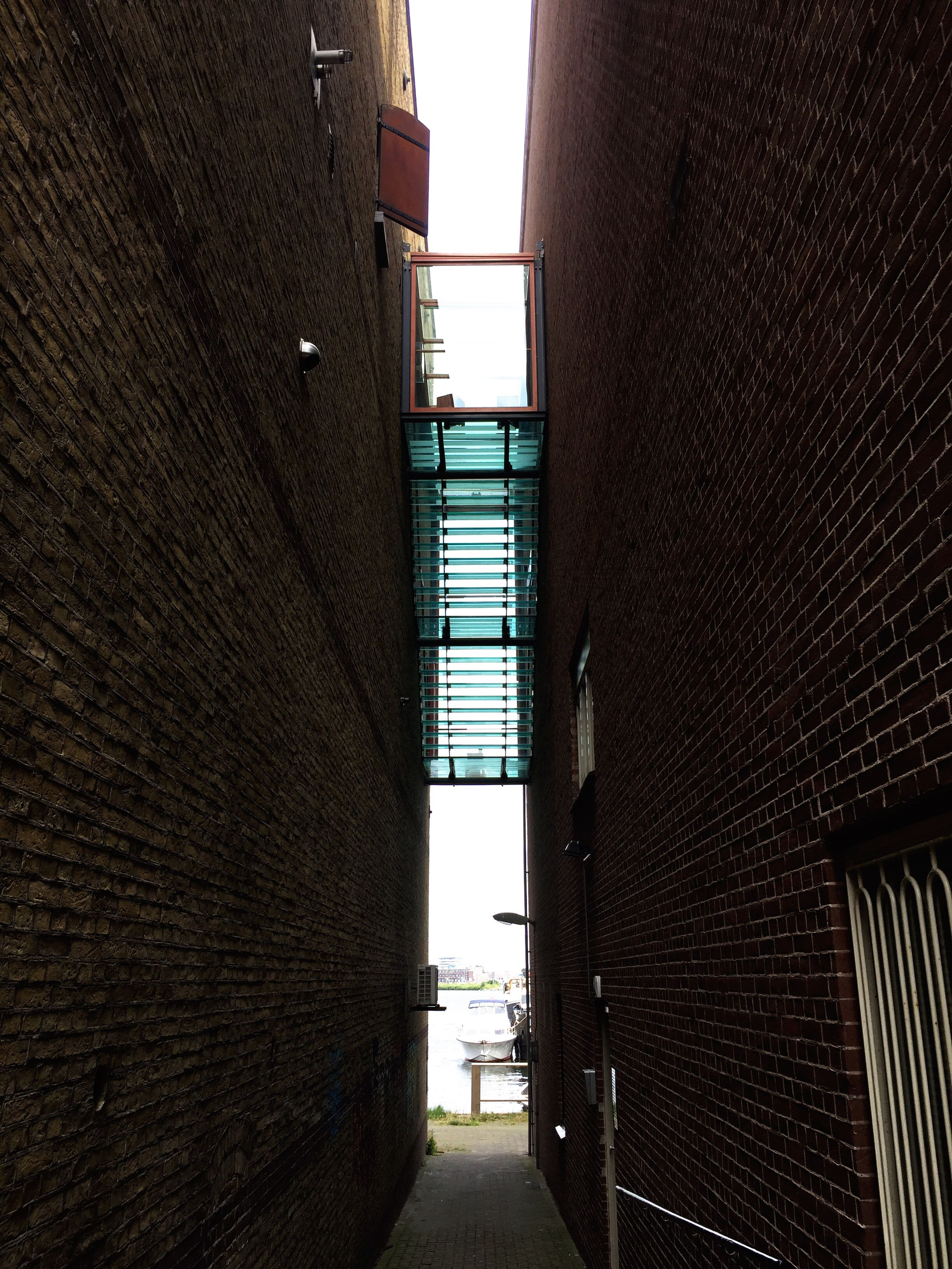 architecture, built structure, the way forward, narrow, building exterior, long, wall - building feature, walkway, day, in a row, clear sky, diminishing perspective, pathway, sky, alley, outdoors, arched, tall, surface level