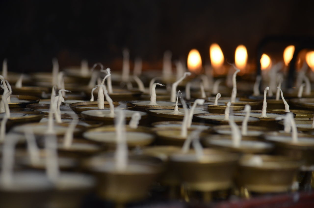 Selective Focus In A Row Surface Level Large Group Of Objects Repetition Tranquility Full Frame Candle Butterlamps Golden Flame Light Culture Nepal Temple Inside Memorial Religion Travel