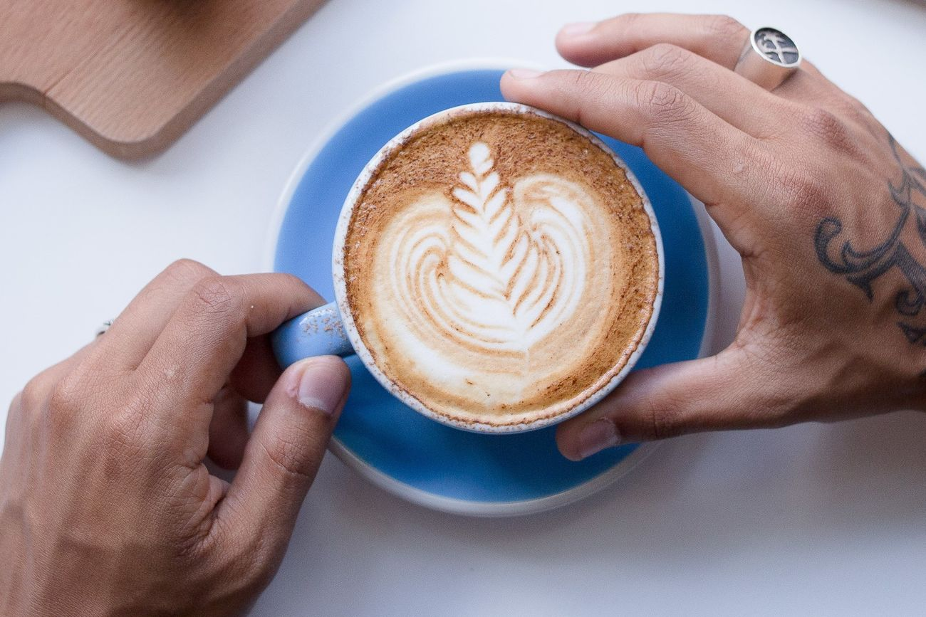 Blue Color Cappuccino Close-up Coffee - Drink Coffee Cup Day Drink Food And Drink Freshness Froth Art Frothy Drink Holding Human Body Part Human Hand Indoors  Latte Lifestyles One Person People Real People Refreshment Saucer Table Tattoo White Background