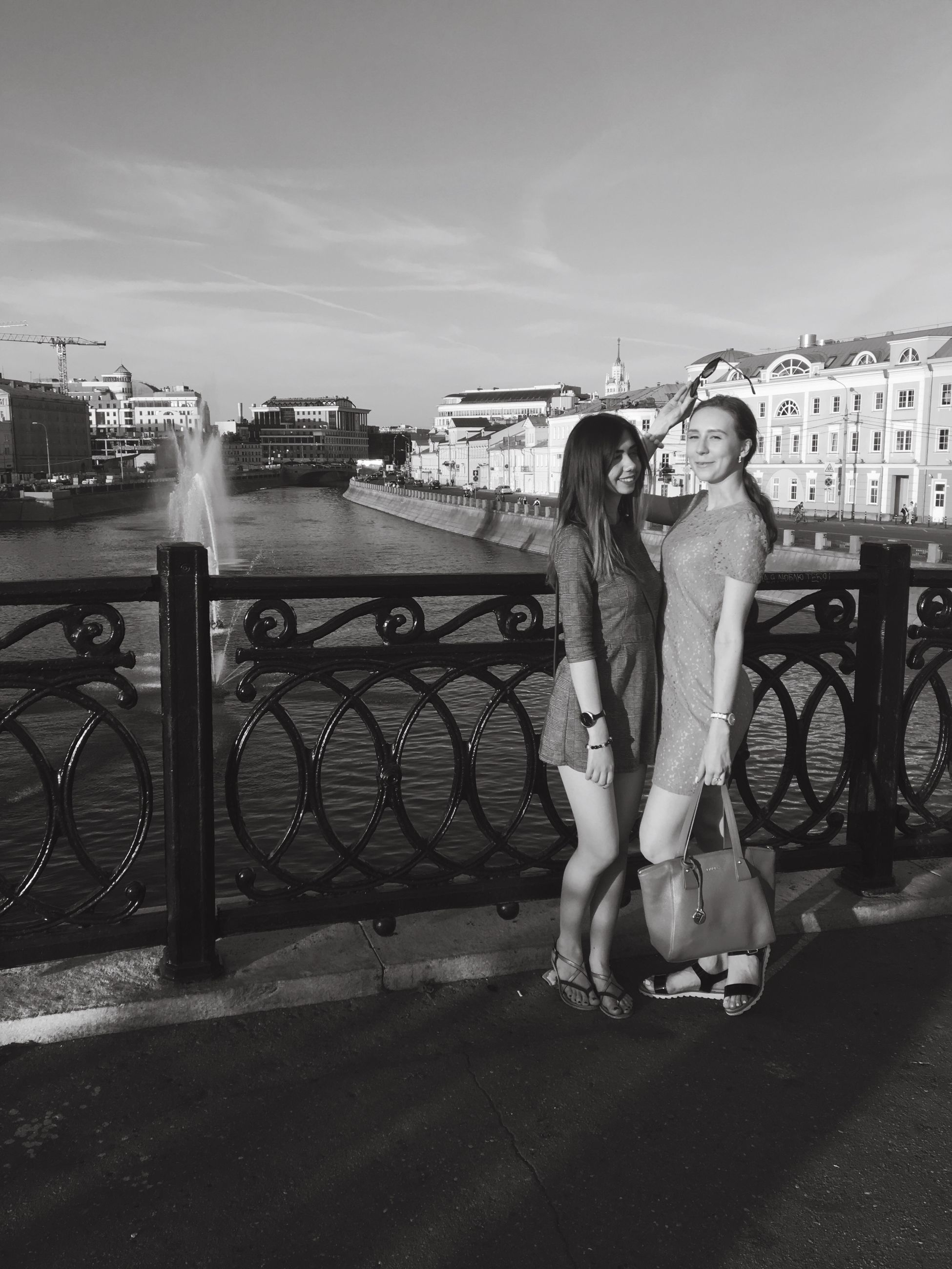 full length, built structure, two people, building exterior, real people, outdoors, young women, architecture, sky, day, city, togetherness, young adult, love, leisure activity, happiness, bridge - man made structure, smiling, retaining wall, lifestyles, bonding, women, friendship, cityscape