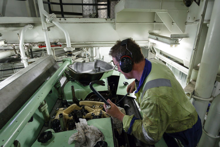 The Second Engineer onboard a British Supply Vessel operating in the North Sea changes an injector on a Rolls-Royce Bergen marine diesel engine. Engine Room PPE Concentration Dexterity Diesel Engine Ear Defenders Expertise Fuel Injectors Hand Tools Indoors  Industry Machinery Maintenance Work Manufacturing Equipment Marine Engineer Occupation One Man Only One Person People Real People Safety Equipment Skill  Supply Ship Work Area Working