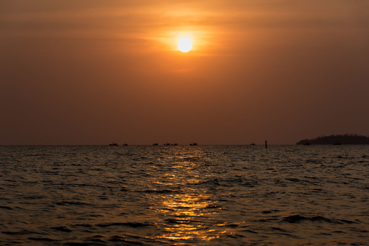 A fleet of Silhouetted Asian fishing boats far on the horizon head out to sea at sunset. Beauty In Nature Calm Catch Fishing Fishing Boat Fleet Horizon Horizon Over Water Island Many No People Orange Outdoors Red Scenics Sea Setting Sun Silhouette Sky Sun Sunlight Sunset Tranquility Water
