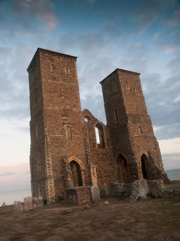 Reculver is a village and coastal resort about 3 miles (5 km) east of Herne Bay in south-east England, in a ward of the same name, in the City of Canterbury district of Kent. It once occupied a strategic location at the north-western end of the Wantsum Channel, a sea lane that separated the Isle of Thanet and the Kent mainland until the late Middle Ages. This led the Romans to build a small fort there at the time of their conquest of Britain in 43 AD, and, starting late in the 2nd century, they built a larger fort, or castrum, called Regulbium, which later became one of the chain of Saxon Shore forts. The military connection resumed in the Second World War, when the sea off Reculver was used for testing Barnes Wallis's bouncing bombs. Ancient Architecture Building Exterior Built Structure Castle Cloud - Sky Day History Kent Medieval No People Old Ruin Outdoors Reculver Reculver Towers Sky Tower Travel Travel Destinations Vivid International