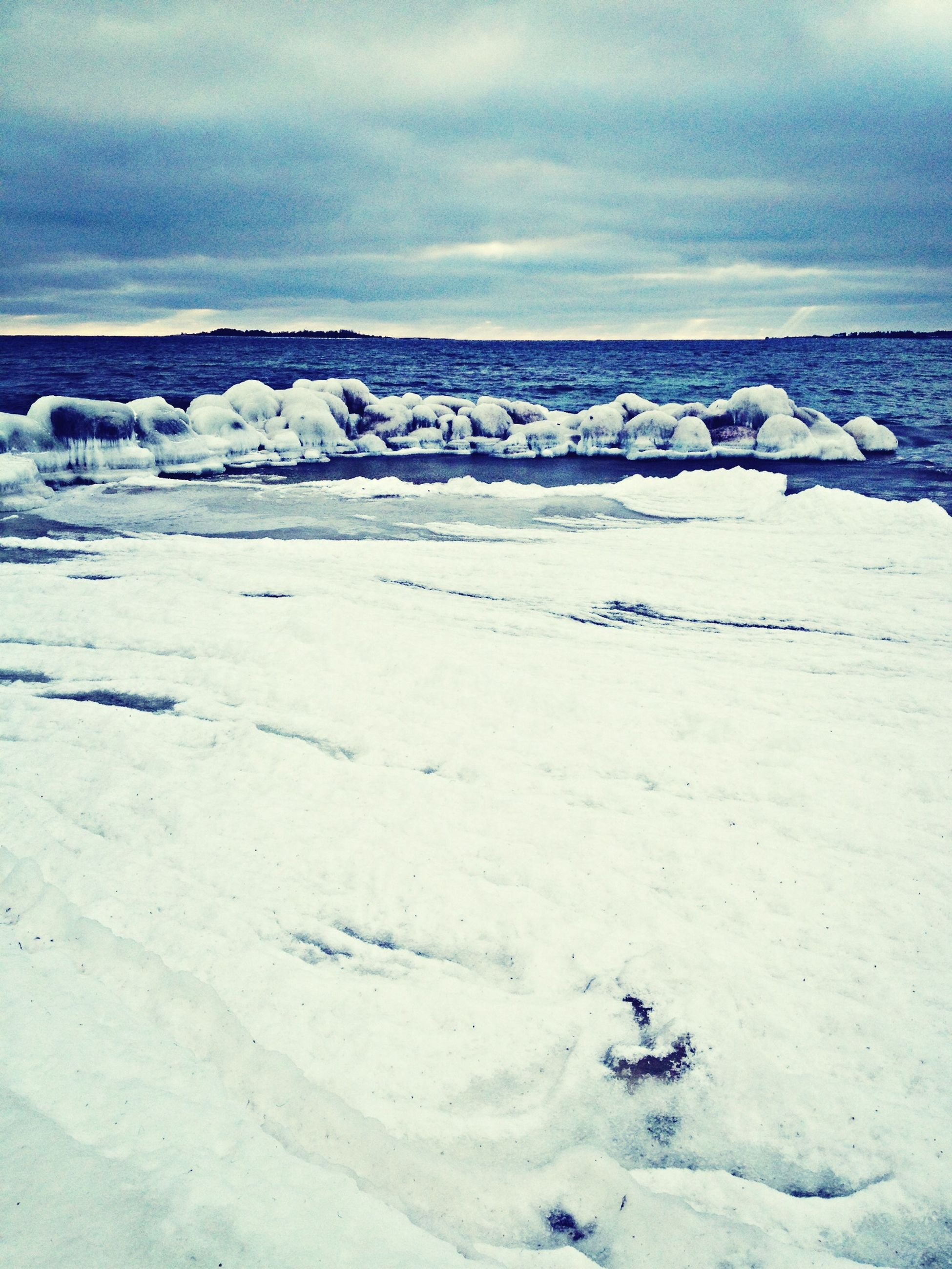 winter, snow, cold temperature, sky, weather, tranquility, nature, sea, tranquil scene, beauty in nature, scenics, cloud - sky, beach, water, horizon over water, sand, day, season, cloud, outdoors