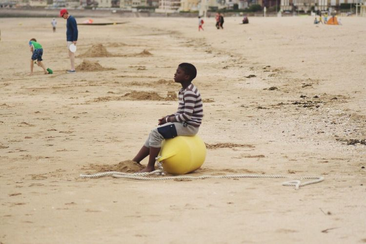 Sand Real People Beach Ball Playing Lifestyles Relaxing Young Person One Person Outdoors Young Boy Young Boy Is Looking Junge Am Strand Strandleben