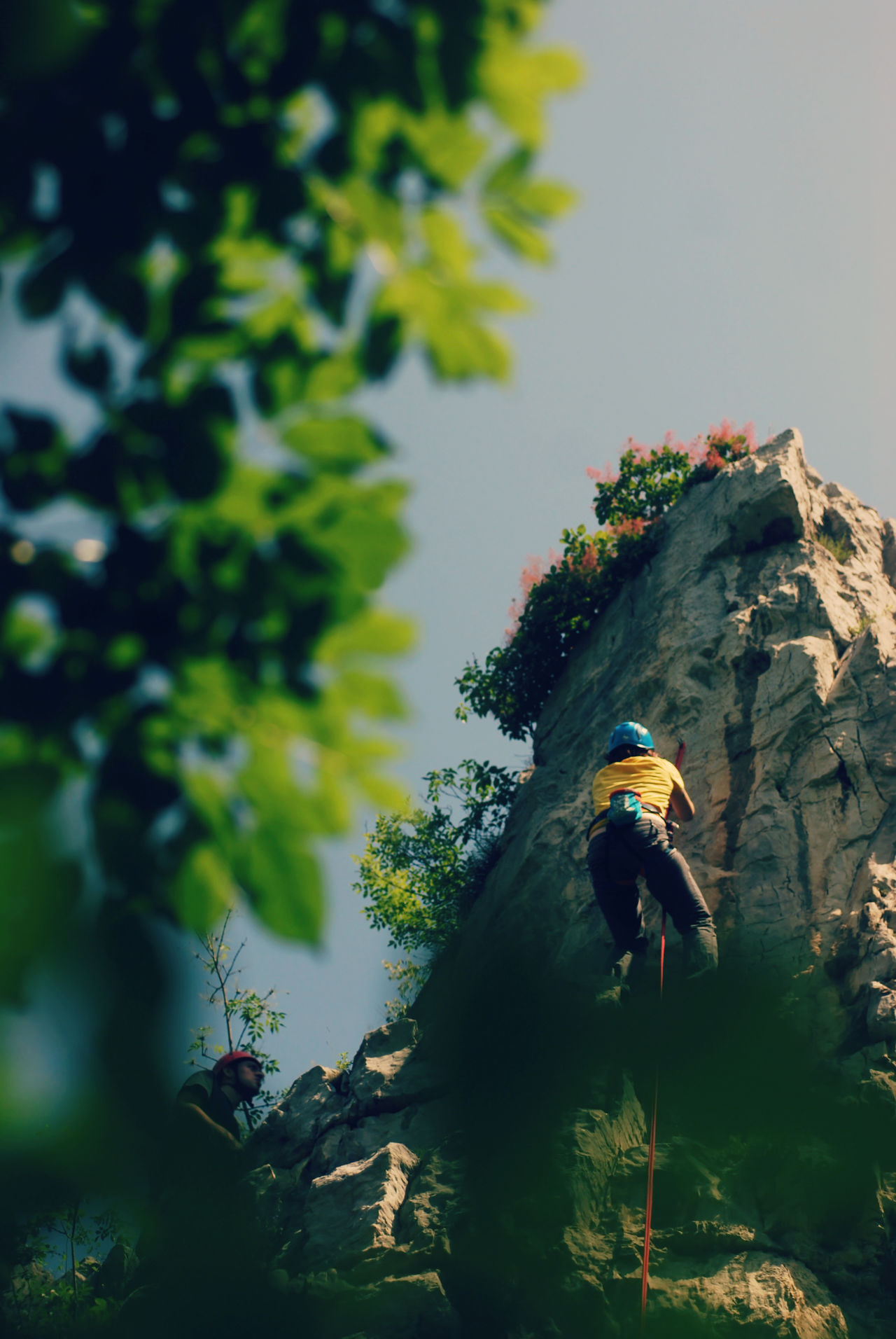 Low angle view - abseiling from a steep rock Abseil Abseiling Activity Adventure Altitude Cliff Descending Extreme Sports Helmet Hills Learning Lifestyle Low Angle View Mountaineering Nature Outdoors Rappel Rappelling Rockclimber RockClimbing Rope Sky Sport Steep Vertical