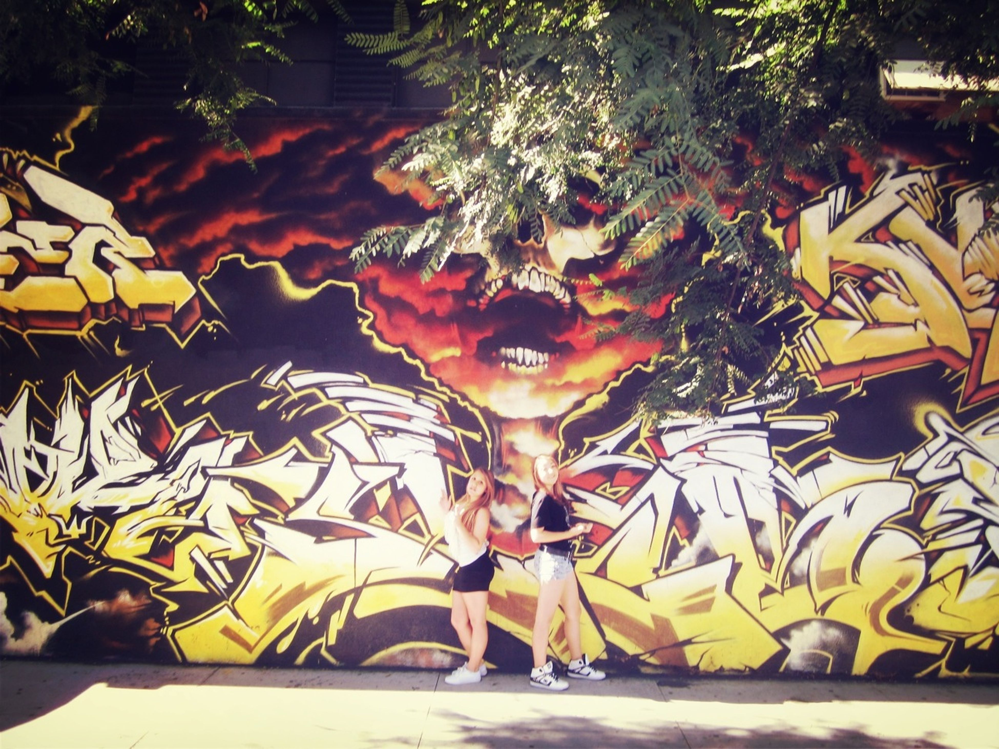 art and craft, art, creativity, tree, graffiti, built structure, architecture, building exterior, yellow, outdoors, day, street, sunlight, no people, wall - building feature, multi colored, park - man made space, incidental people, shadow, street art