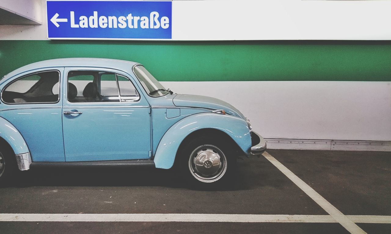 Blue VW beetle at a parking lot Car Transportation Text Street Communication Road Sign Road Land Vehicle Day Outdoors No People Concrete Concrete Wall Concrete Floor Parking Lot Parking Parking Area Parking Space VW VW Beetle VW Käfer Blue Shopping Mall Shopping Time