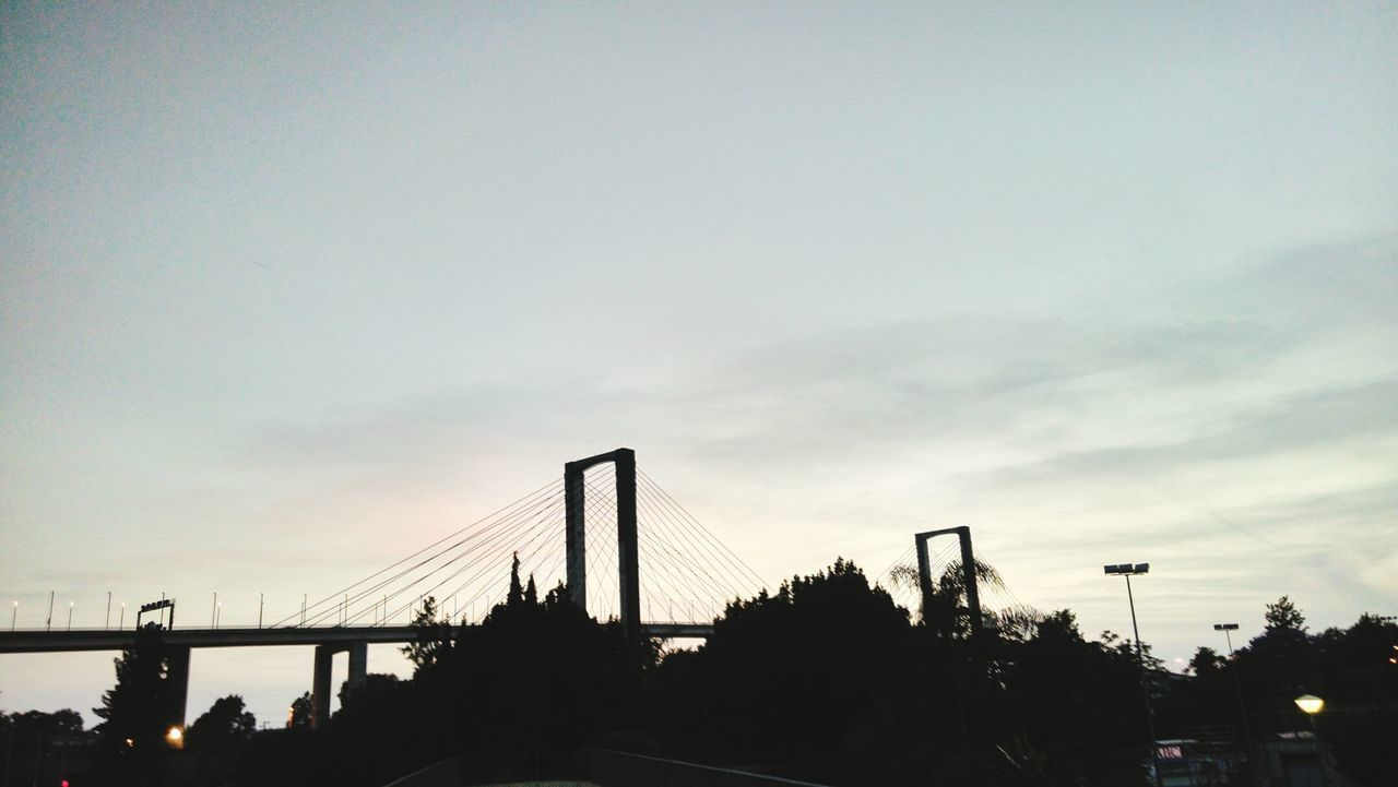 architecture, built structure, sky, bridge - man made structure, connection, suspension bridge, city, silhouette, bridge, building exterior, skyscraper, transportation, outdoors, tree, sunset, travel destinations, no people, modern, day