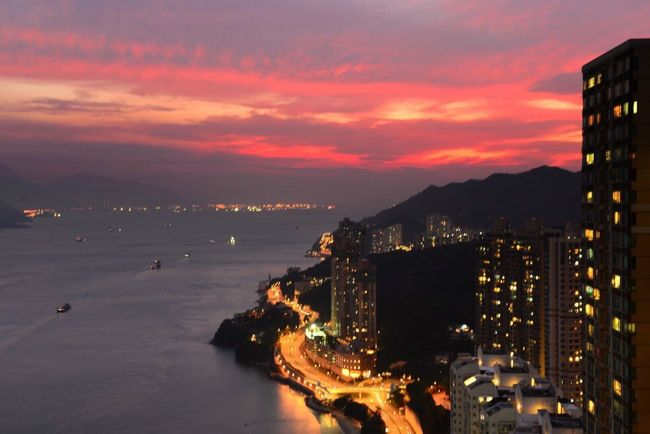 Sunset Illuminated Scenics Water Architecture Sea Built Structure Building Exterior Cloud - Sky Sky City Beauty In Nature Cityscape Tranquil Scene Tranquility Orange Color Cloud Nature Dramatic Sky Shore