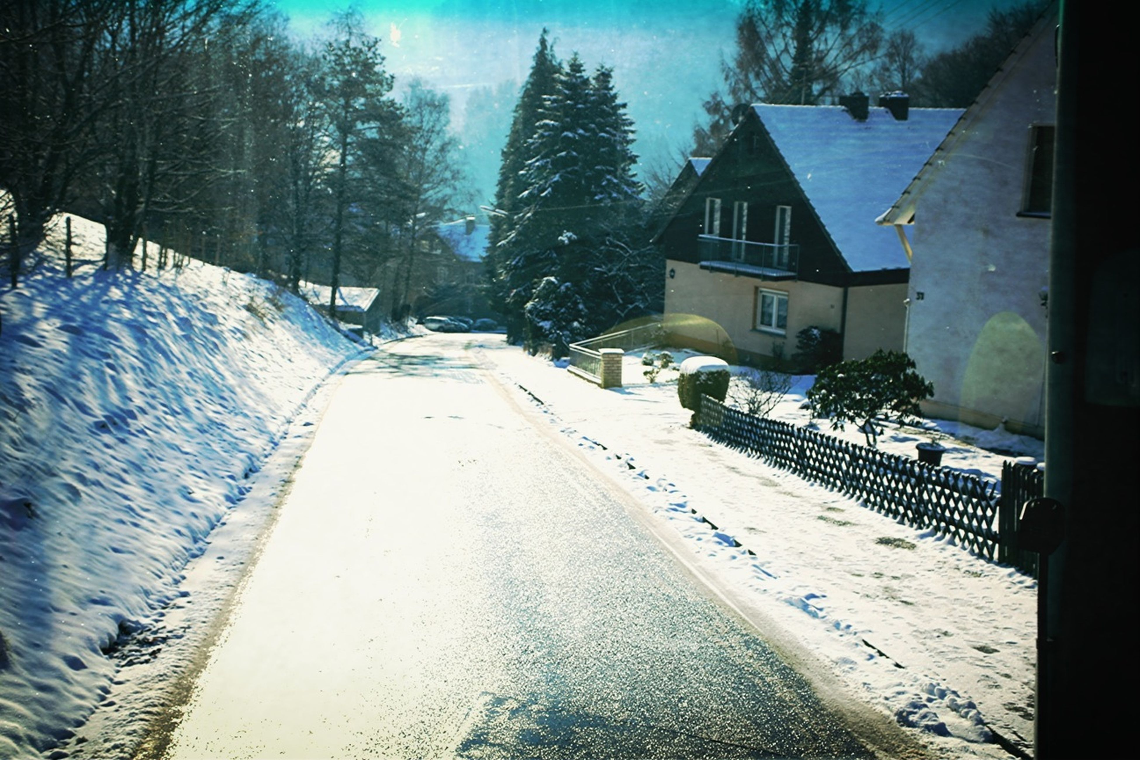 snow, cold temperature, winter, building exterior, the way forward, architecture, built structure, season, house, diminishing perspective, covering, weather, street, residential structure, vanishing point, residential building, tree, road, sky, covered