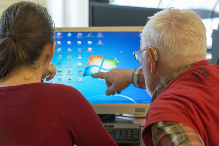 Older gets computer lessons from younger ones Lessons The Netherlands Adult Casual Clothing Close-up Communication Computer Computer Lessons Day Domestic Animals Dutch Indoors  Leisure Activity Men People Real People Rear View Sitting Technology Togetherness Two People Women