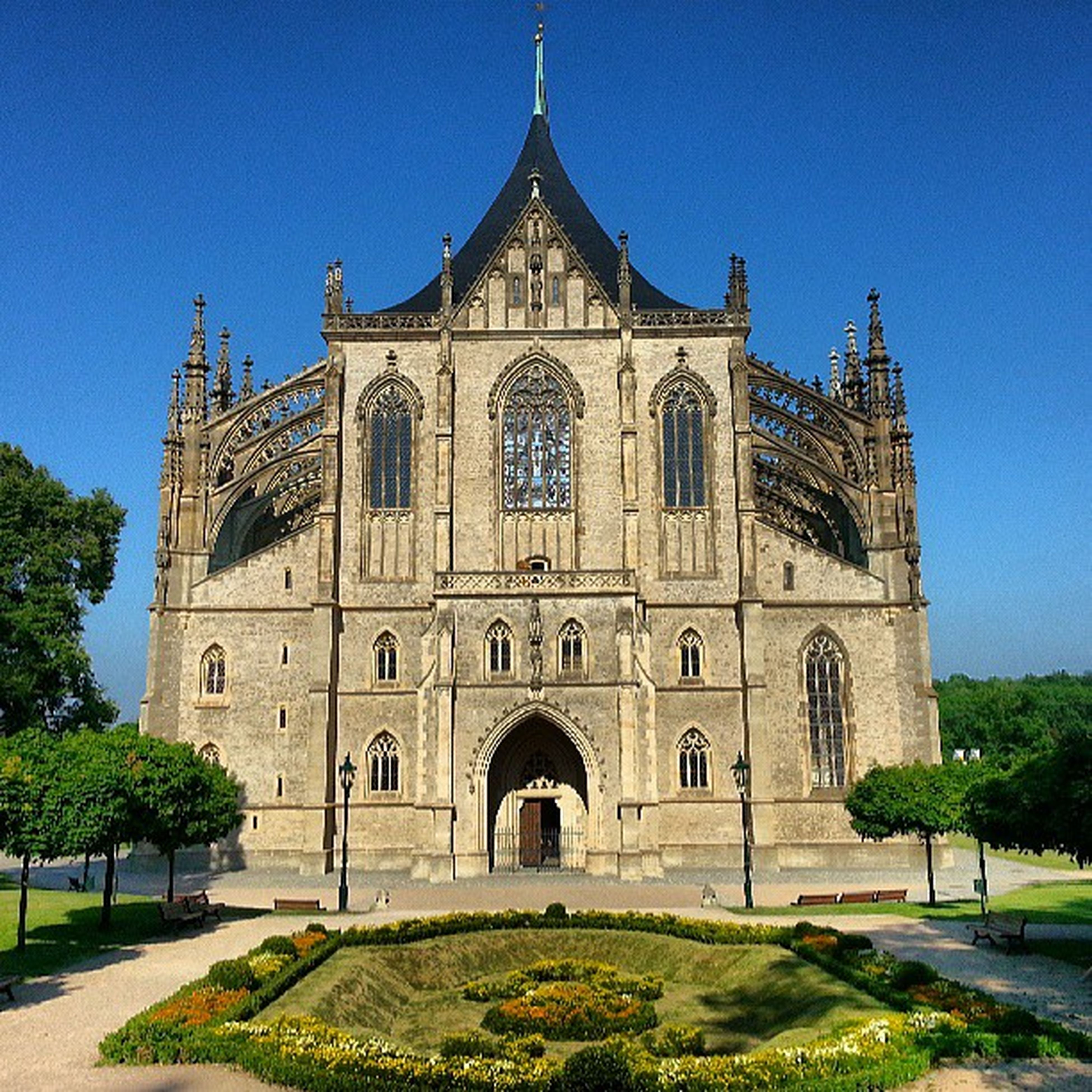 architecture, building exterior, built structure, place of worship, religion, church, facade, clear sky, tree, blue, spirituality, lawn, low angle view, grass, arch, sunlight, sky, cathedral