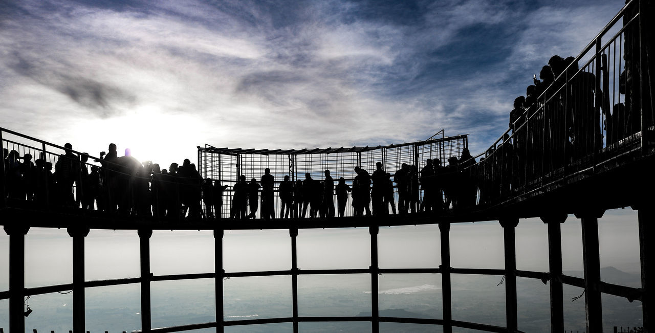 railing, sky, large group of people, built structure, architecture, bridge - man made structure, connection, cloud - sky, real people, silhouette, outdoors, men, travel destinations, building exterior, women, day, water, city, nature, people