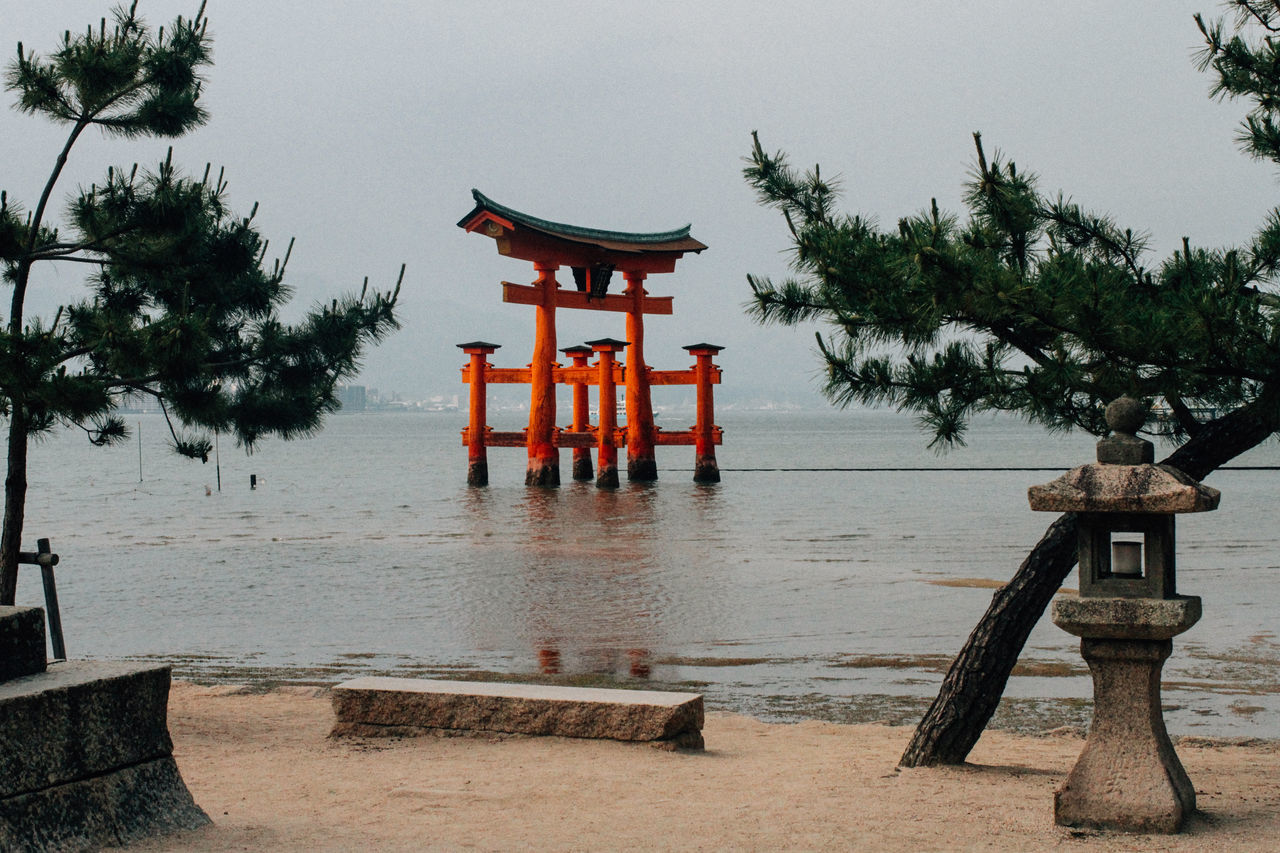 Architecture Cultures Day Japanese Gate Japanese Style No People Outdoors Pine Tree Place Of Worship Red Religion Sculpture Shrine Spirituality Statue Tori Torii Gate Travel Travel Destinations Tree Water