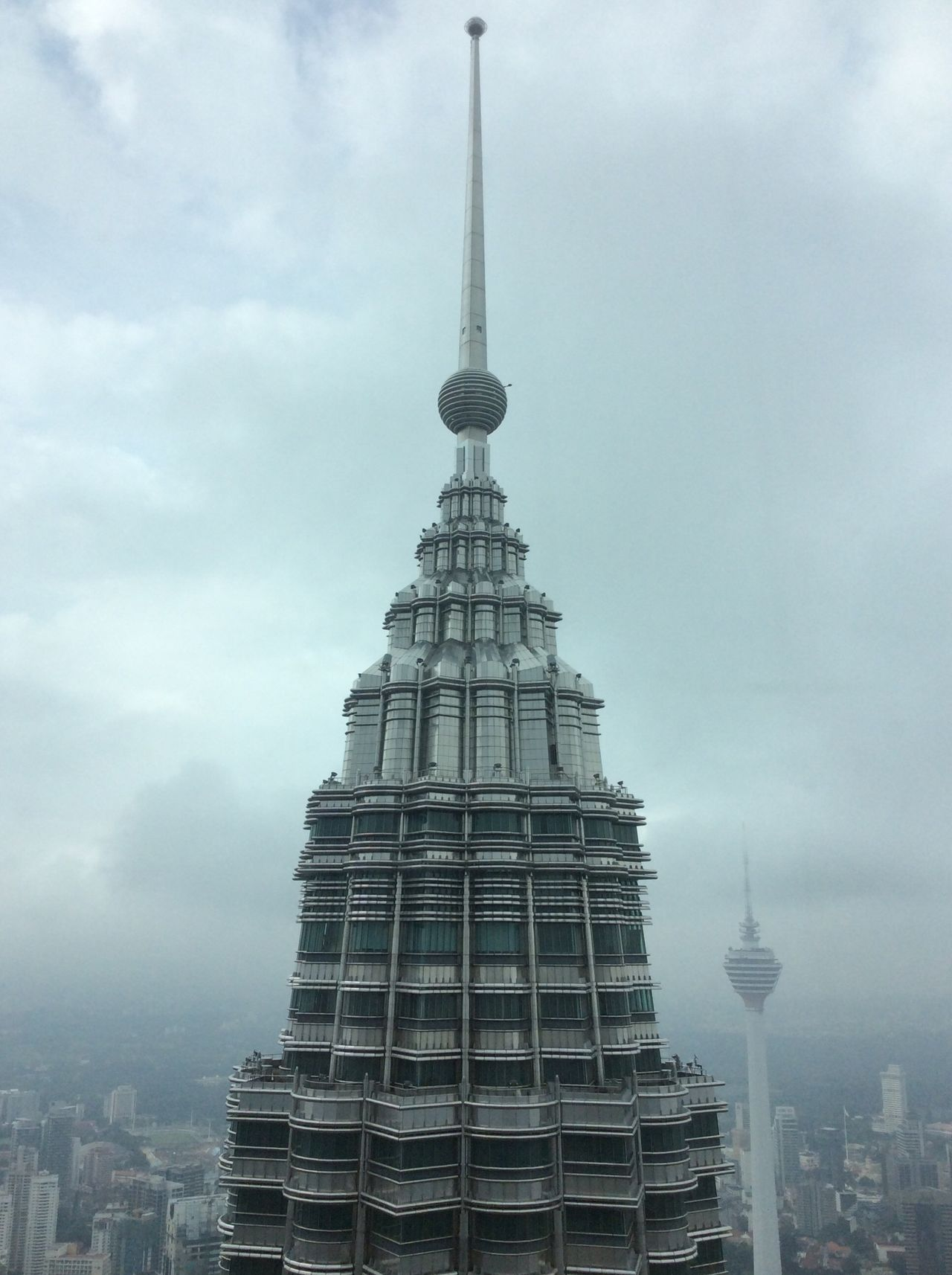 Top of the Patronas Twin Tower Modern Contemporary Architecture with KL tower in the background Grey Skies Pinnicle City Landscape