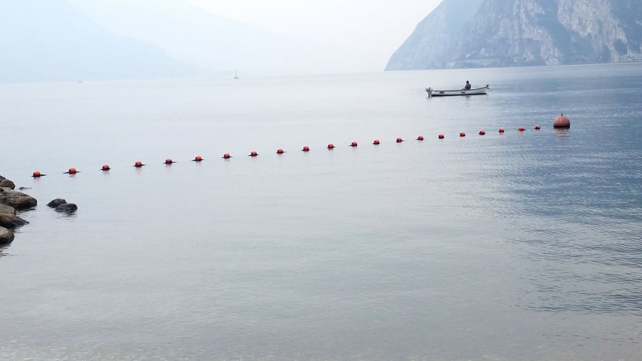 IN A ROW, by Claudia Ioan Nature Water Beauty In Nature Tranquility Outdoors Day Mountain Fog Sky No People Landscape Lake Lake Garda Tranquil Scene