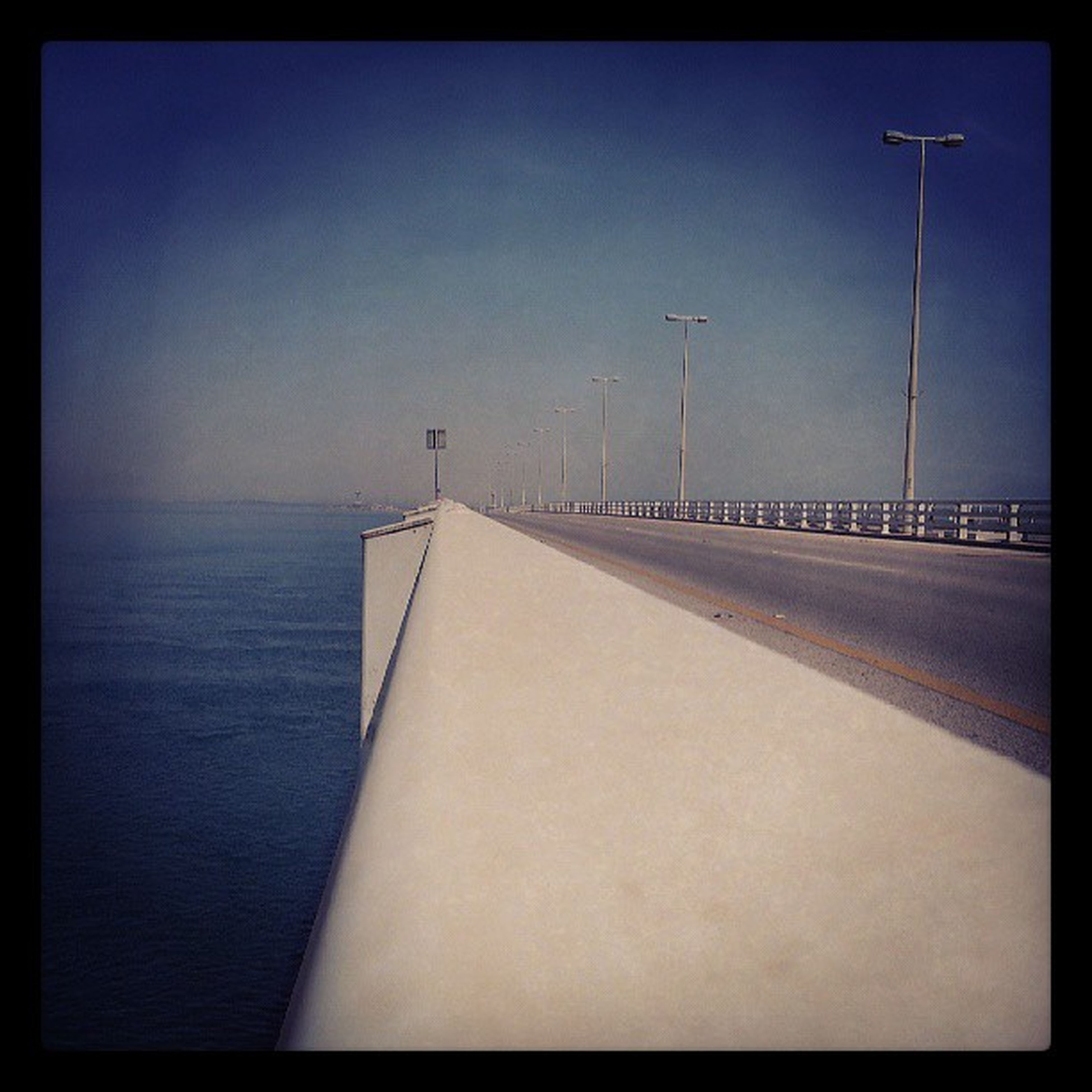 transfer print, sea, auto post production filter, water, the way forward, sky, horizon over water, clear sky, copy space, tranquility, transportation, tranquil scene, street light, built structure, diminishing perspective, outdoors, nature, vanishing point, empty, no people
