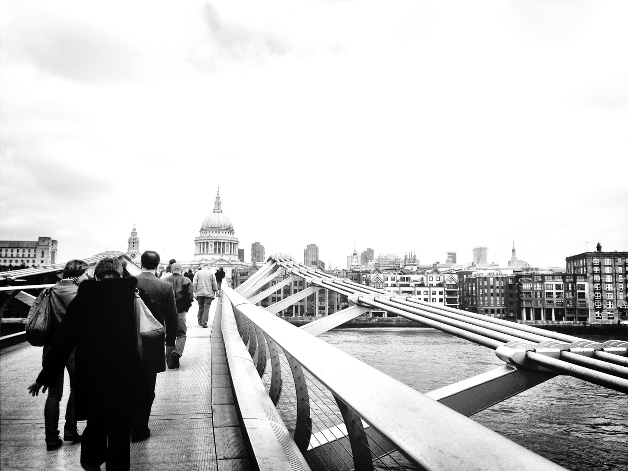 architecture, built structure, building exterior, men, city, walking, person, lifestyles, rear view, city life, railing, clear sky, sky, leisure activity, bridge - man made structure, large group of people, travel destinations, travel, copy space