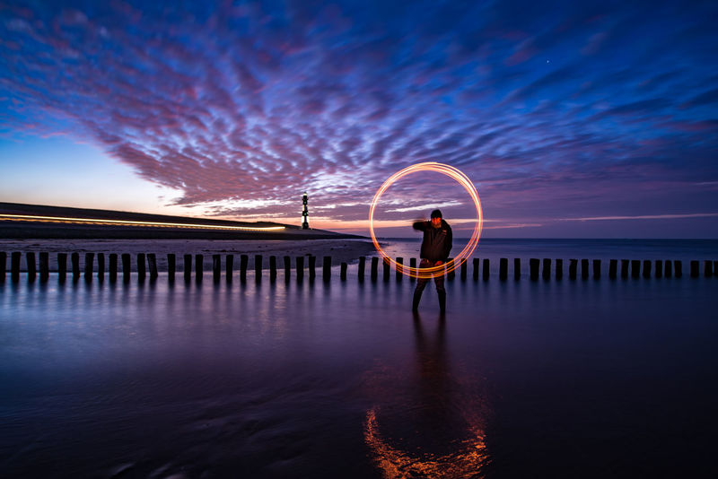 """Self portrait on the beach this evening. The sky was amazing again and the setting of Breskens beach is one of my favorite. But at sub zero temperatures, it was just too cold to try out all my idea's. I'll be back... (Nikon D810 14-24mm f/2.8 ƒ/3.2 17.0 mm 15"""" iso 31) Beach Breskens Dusk Europe Evening Fire Landscape Long Exposure Netherlands Reflection Sea Self Portrait Spinning Steel Wool Sunset Winter Lost In The Landscape"""