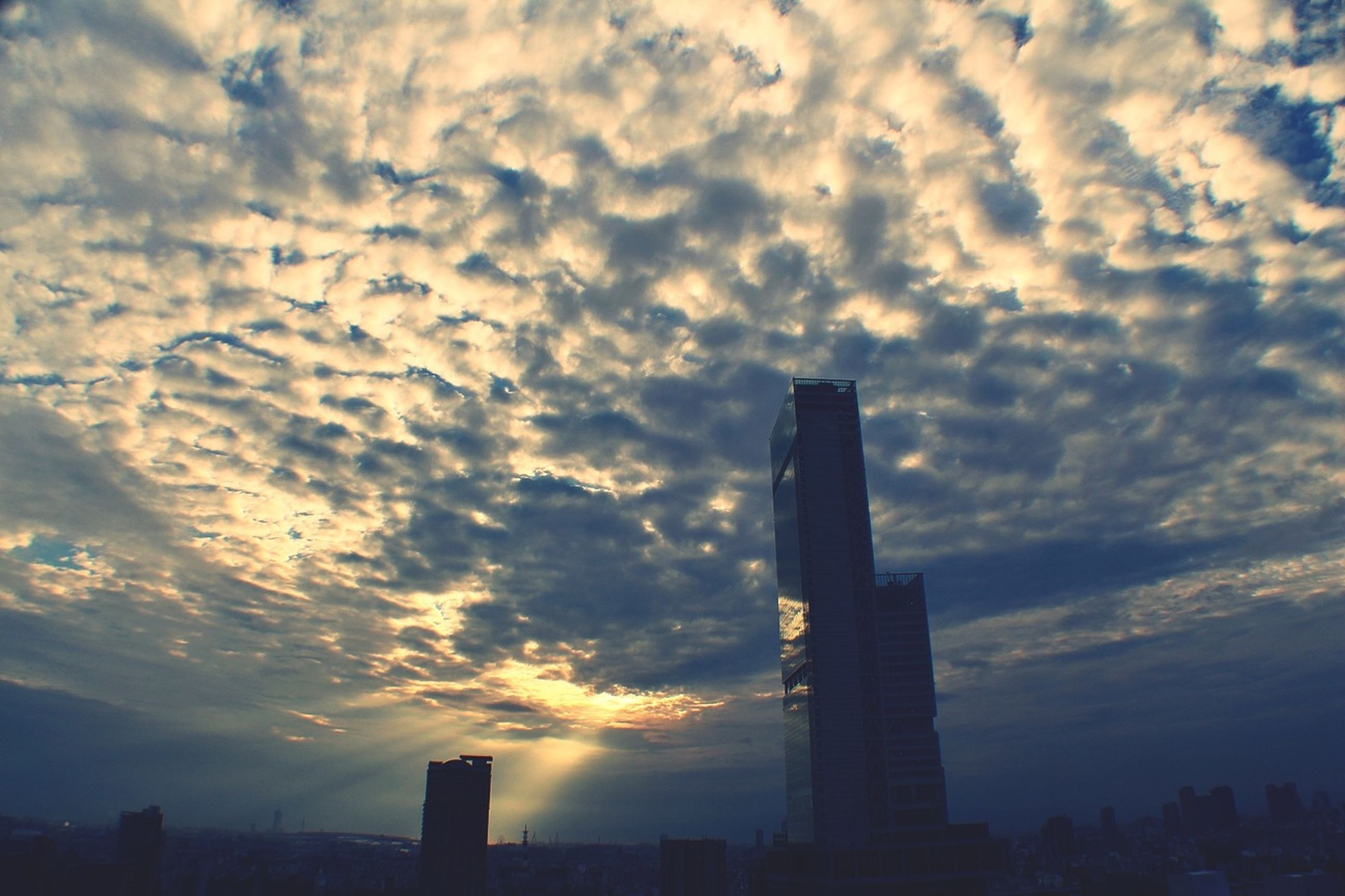 building exterior, architecture, sunset, sky, built structure, city, cloud - sky, silhouette, skyscraper, cloudy, cityscape, cloud, urban skyline, tall - high, tower, building, orange color, low angle view, office building, modern