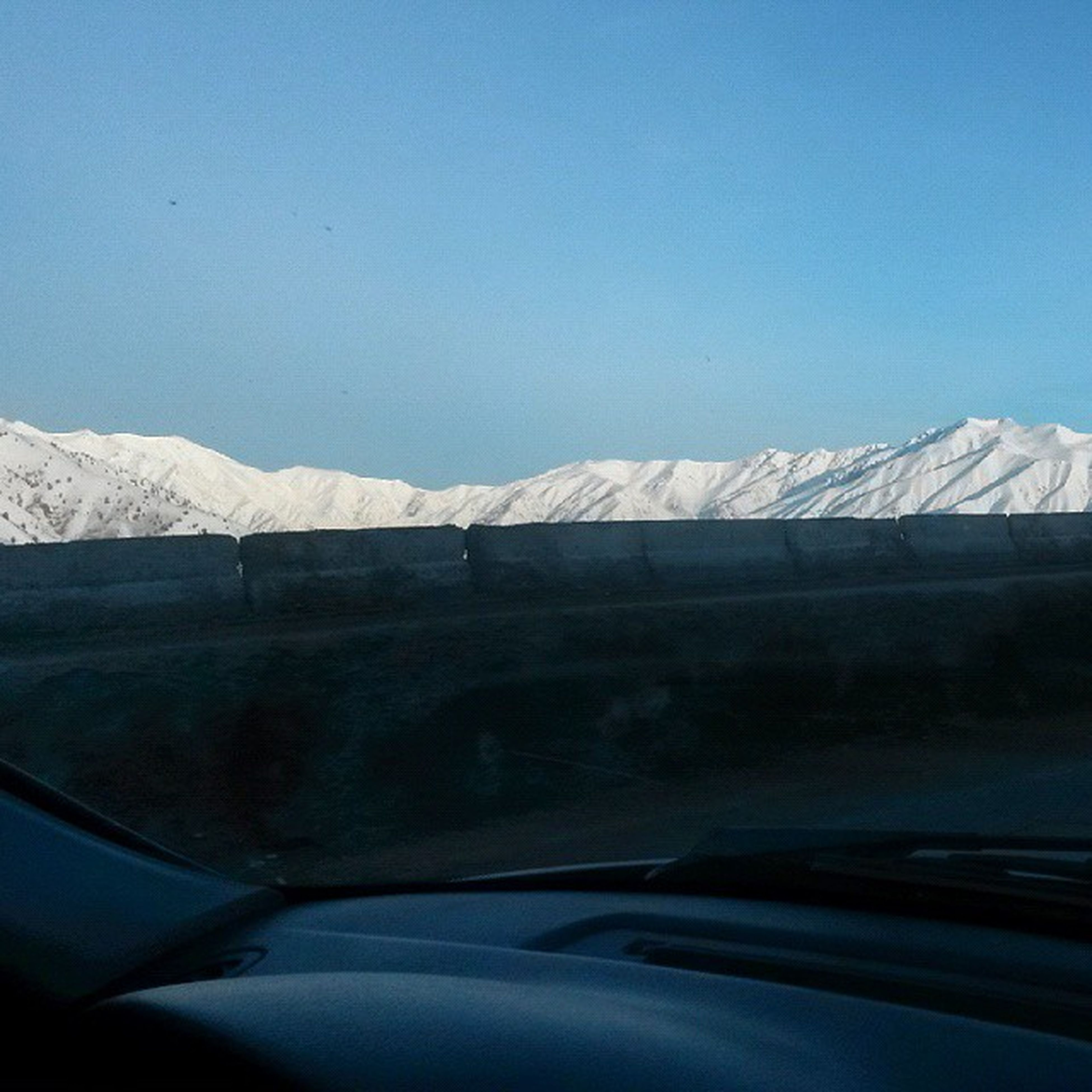 transportation, snow, winter, clear sky, mode of transport, cold temperature, blue, mountain, car, road, copy space, vehicle interior, land vehicle, windshield, glass - material, season, transparent, snowcapped mountain, travel, part of