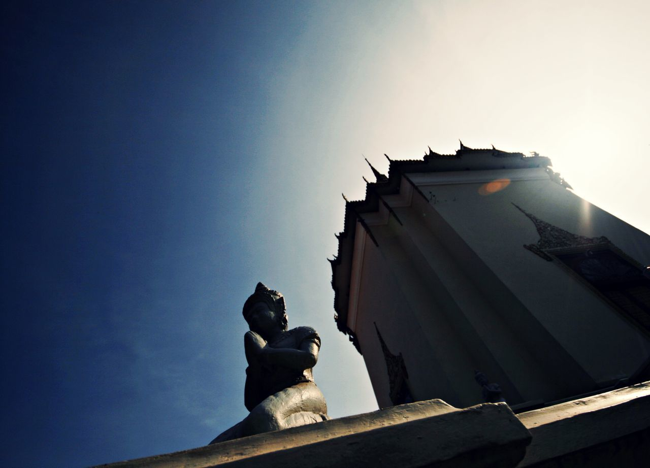 Low angle view of Buddha statue and temple against sky