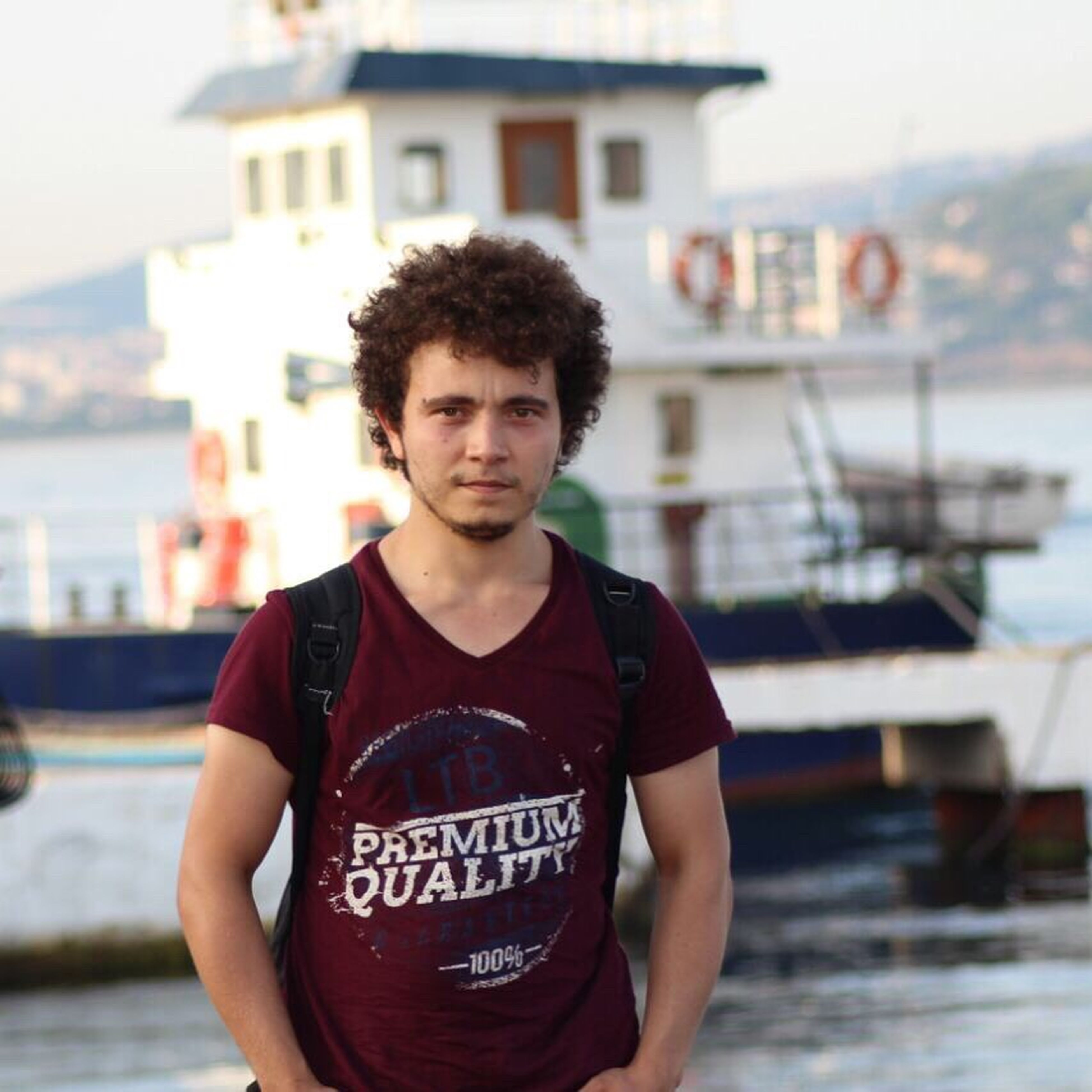 focus on foreground, standing, building exterior, young adult, casual clothing, water, architecture, front view, built structure, leisure activity, lifestyles, handsome, three quarter length, sea, in front of, looking at camera, person, city life