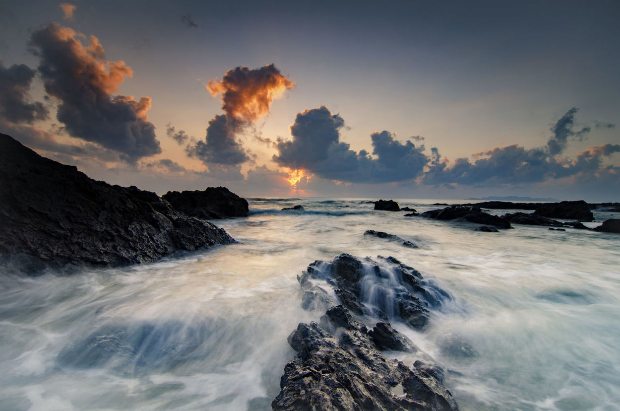 beautiful waves splashing on unique rocks formation at Pandak Beach located in Terengganu,Malaysia over stunning sunrise background.soft focus image due to long exposure Beach Photography Beauty In Nature Cloud - Sky Clouds And Sky Magic Hour Magical Light Malaysia Nature Rock Formation Scenics Sea Sky Splashing Stunning Collection Sunlight Sunrise Sunset Sunshine Tourism Tranquil Scene Waves, Ocean, Nature Wet Rocks White Waves