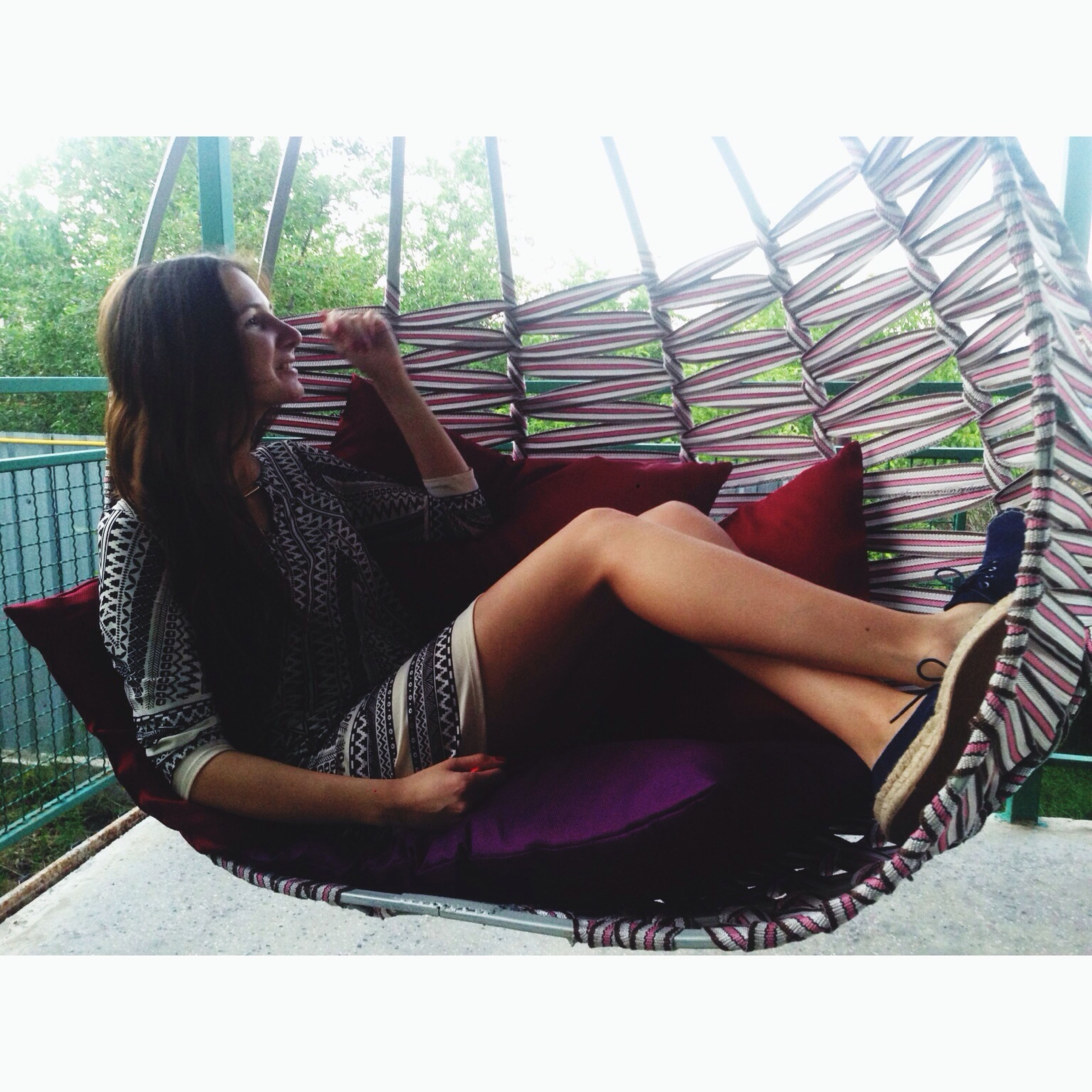 lifestyles, young adult, young women, relaxation, leisure activity, sitting, casual clothing, long hair, person, indoors, sensuality, railing, chair, full length, day, side view