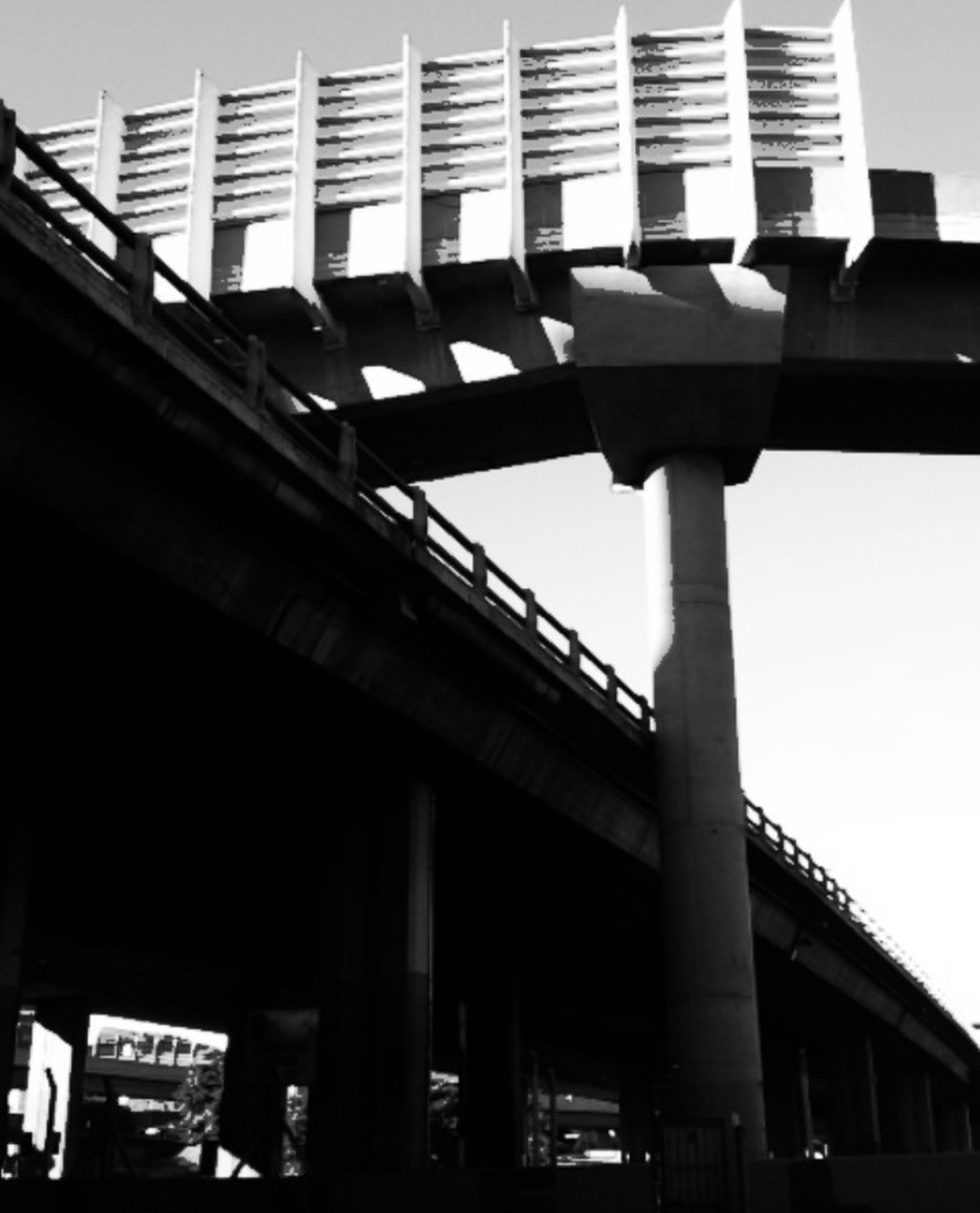 architecture, built structure, low angle view, building exterior, city, connection, clear sky, bridge - man made structure, modern, building, engineering, architectural column, sky, outdoors, no people, day, transportation, street light, city life, bridge