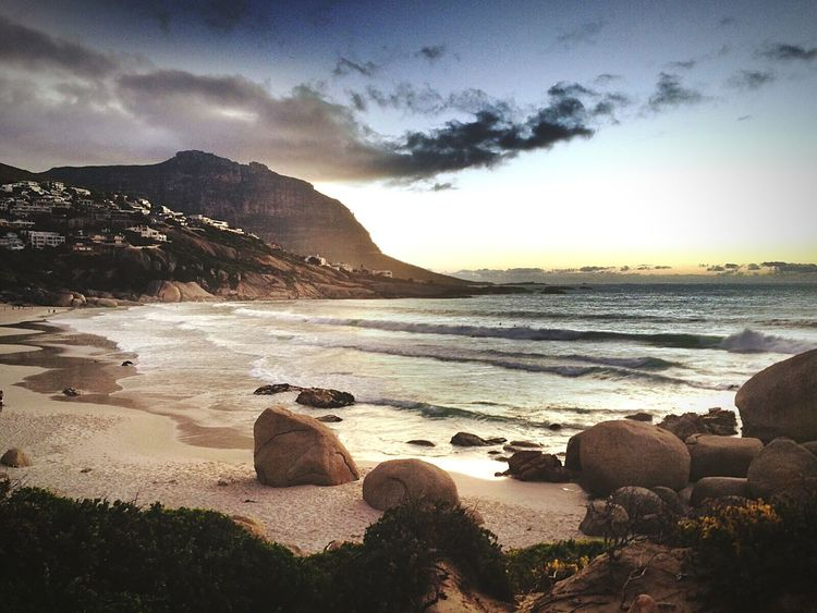 Sea Beauty In Nature Mountain Beach Rock - Object Tranquility Idyllic Tourism Water Sea Tranquil Scene Scenics Sunset Tranquility Sky Beauty In Nature Shore Mountain Rock - Object Beach Nature Non-urban Scene Vacations Idyllic Majestic
