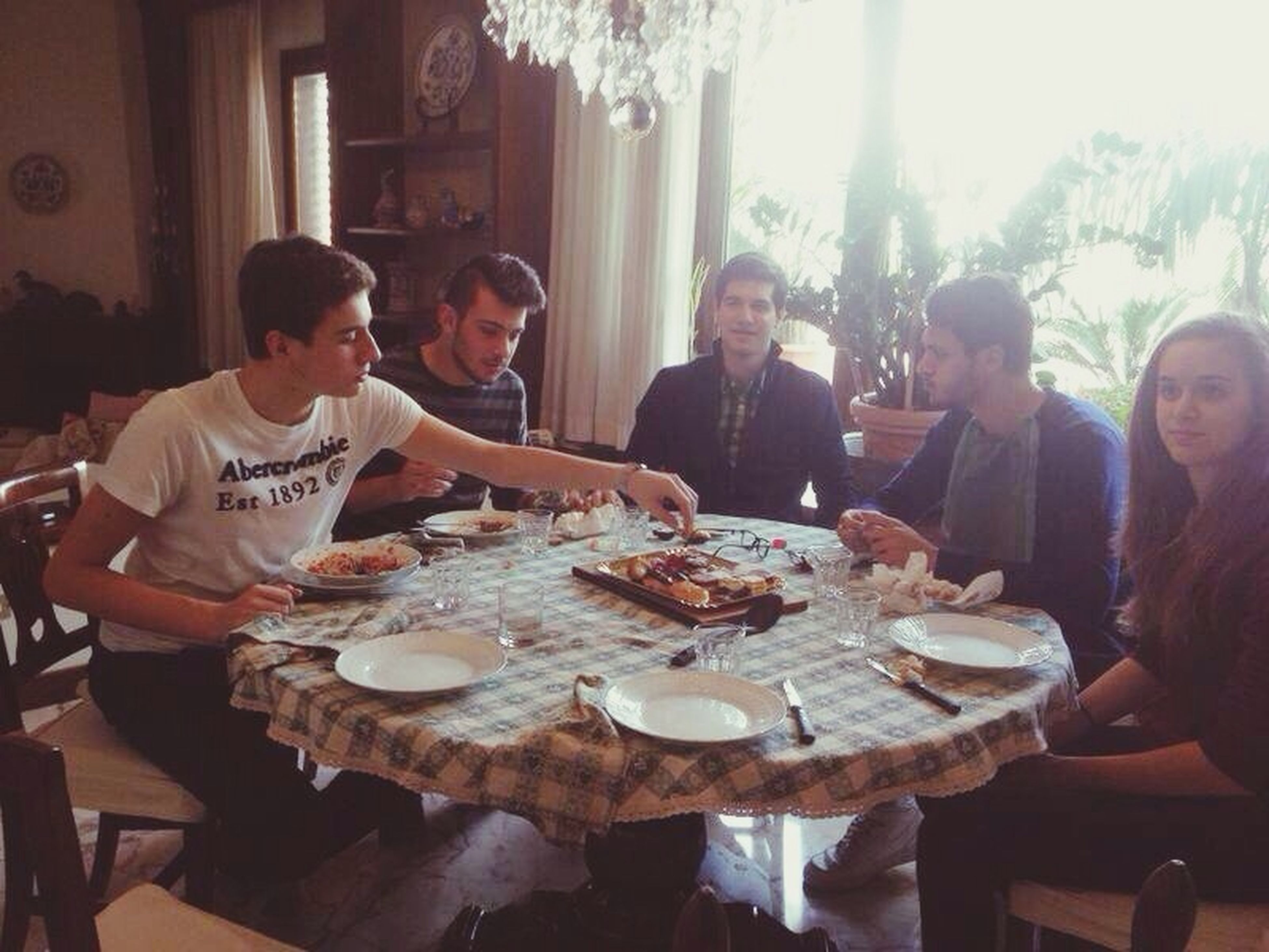 food and drink, indoors, lifestyles, food, leisure activity, table, freshness, togetherness, restaurant, men, sitting, plate, friendship, casual clothing, holding, young men, healthy eating