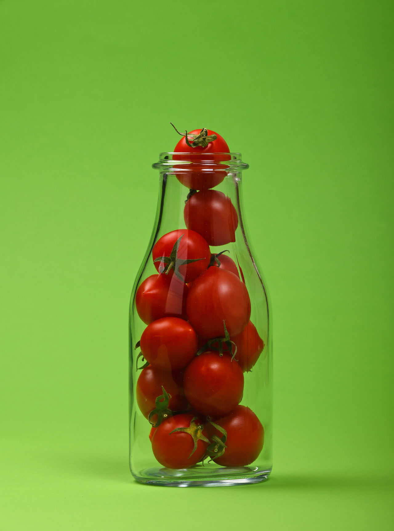 Small red cherry tomatoes in glass bottle over green background Advertising Bottle Cherry Tomato Cherry Tomatoes Colored Background Concept Copy Space Food Freshness Glass - Material Glass Bottle Green Background Green Color Healthy Healthy Eating Juice Ketchup Natural Nature Organic Red Studio Shot Tomato Vegetable Vegetarian Food