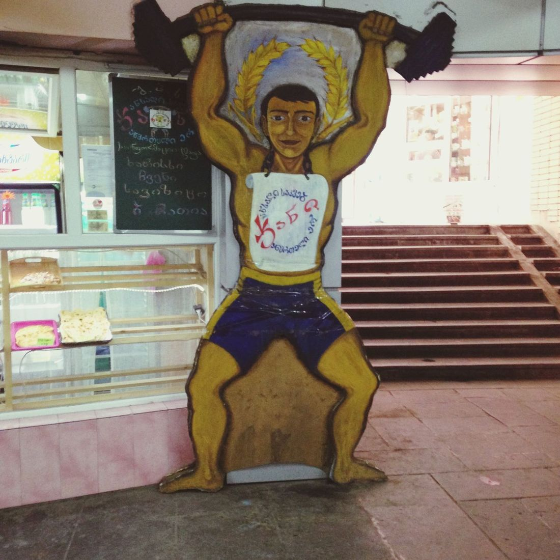 Tbilisi Jani-Jani. Figure of a man lifting weights - his t-shirt says something about healthy food.