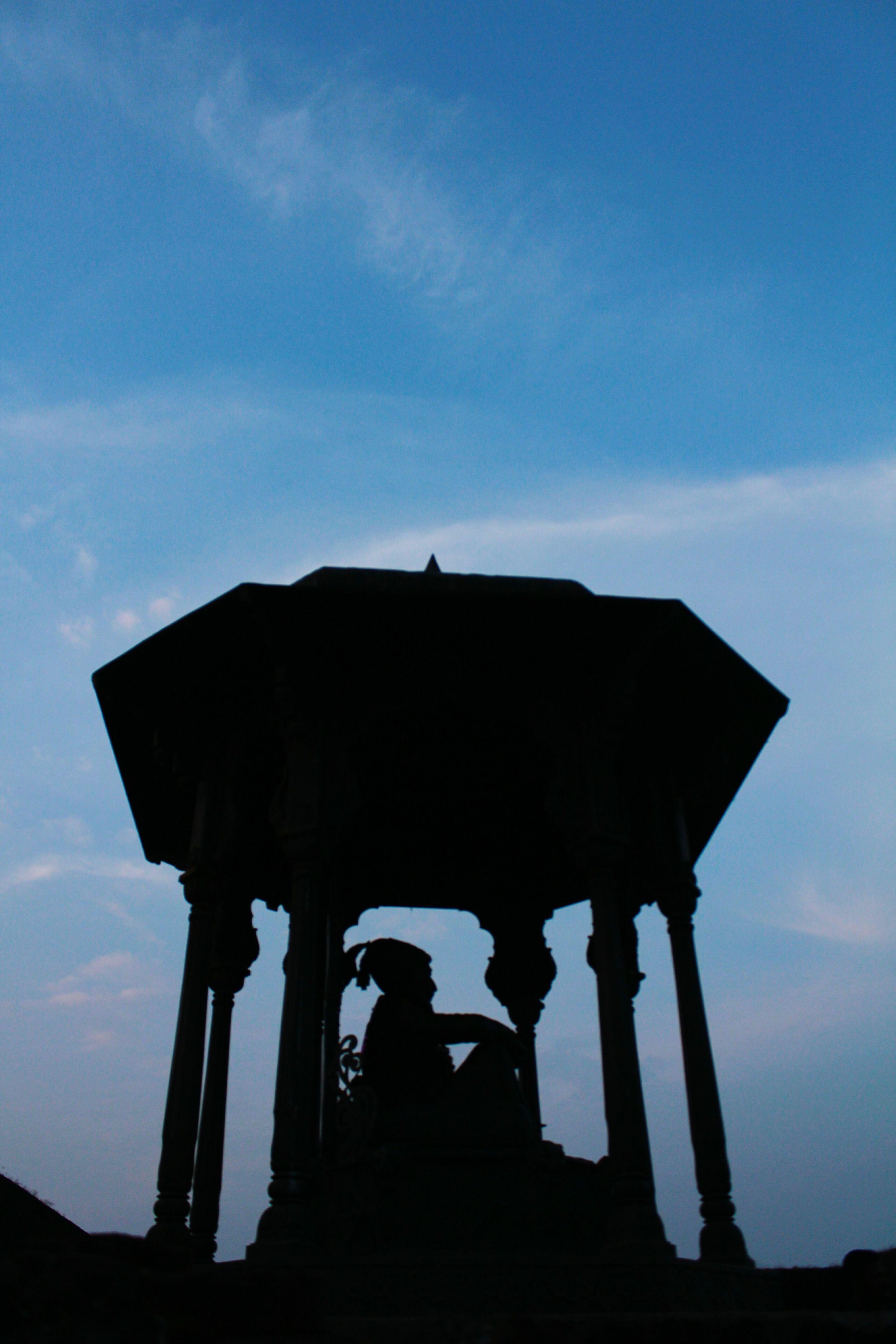 sky, silhouette, low angle view, architecture, built structure, cloud - sky, history, cloud, sunset, spirituality, religion, dusk, building exterior, architectural column, sculpture, statue, place of worship, famous place, outdoors, travel destinations