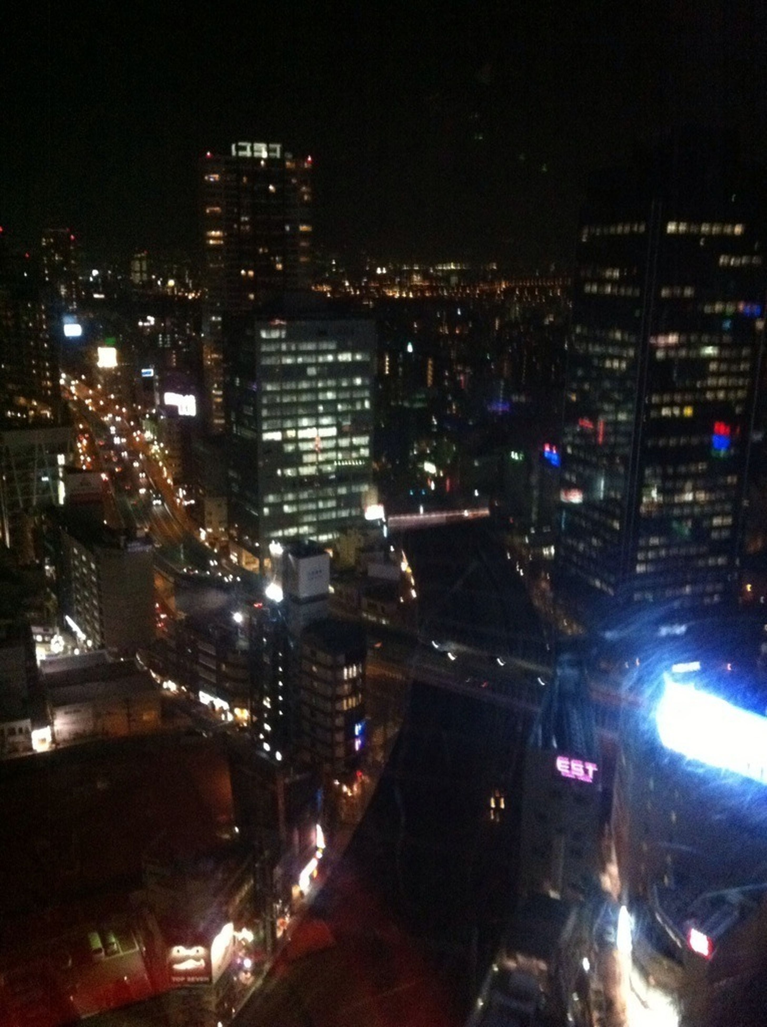 illuminated, night, city, building exterior, architecture, built structure, transportation, car, street, land vehicle, city street, city life, high angle view, cityscape, traffic, road, mode of transport, street light, skyscraper, lighting equipment
