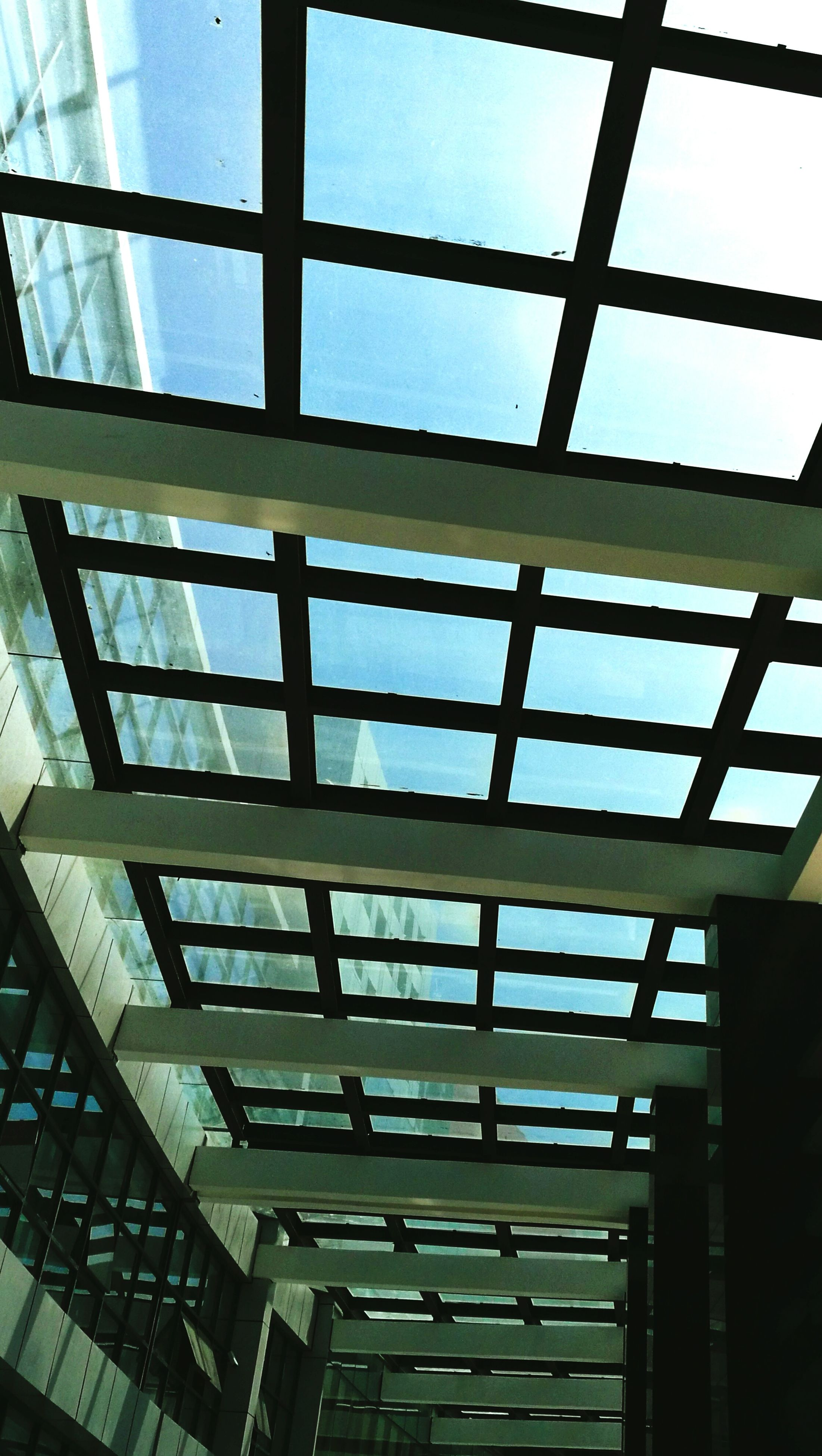 architecture, built structure, glass - material, low angle view, window, building exterior, modern, transparent, indoors, building, sky, glass, reflection, city, office building, day, pattern, no people, architectural feature, ceiling