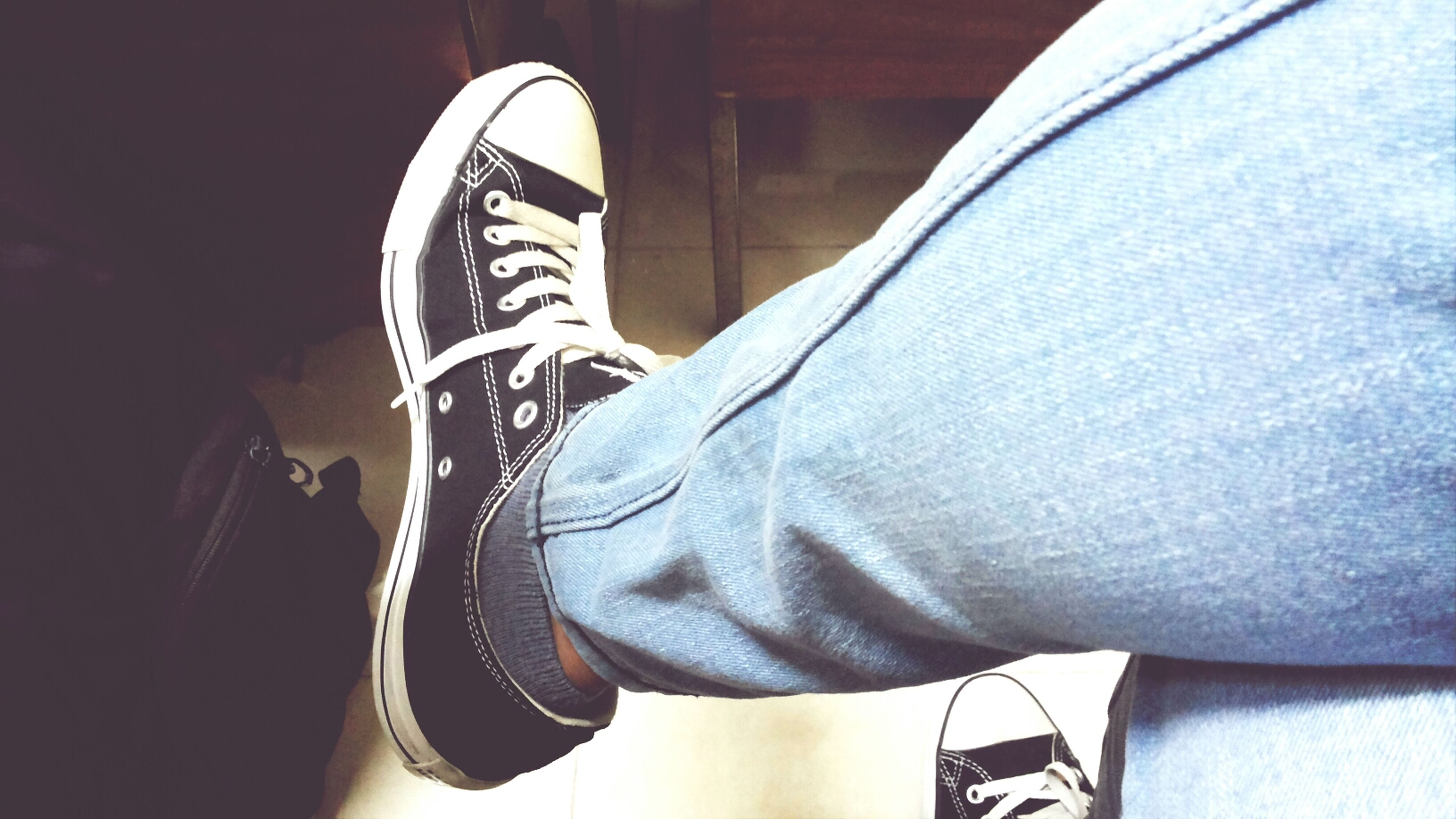 low section, person, lifestyles, indoors, personal perspective, jeans, men, shoe, leisure activity, casual clothing, human foot, sitting, footwear, relaxation, standing, part of