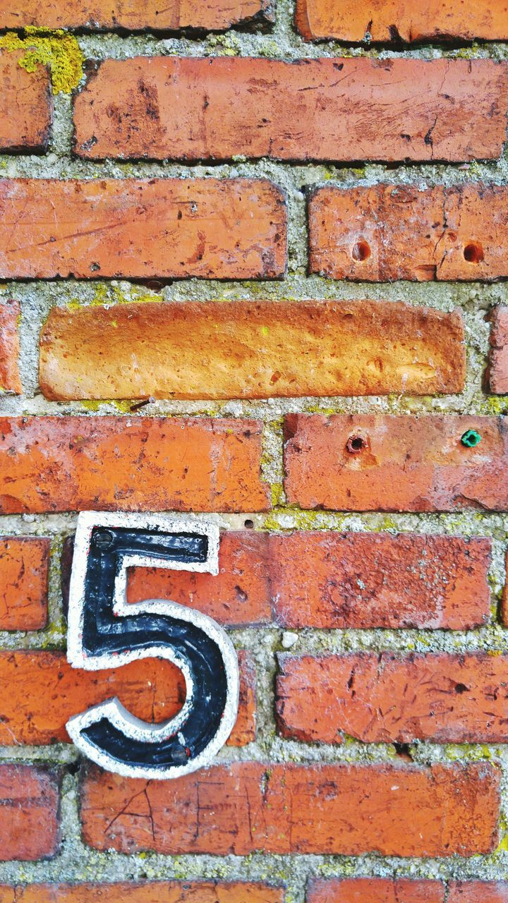 Close-Up Of Number 5 On Brick Wall