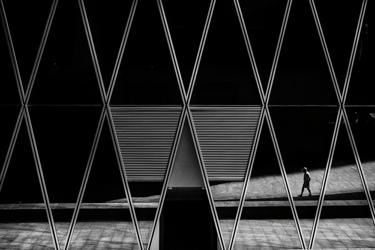 In Between. Night Illuminated Pattern Metal Built_Structure Backgrounds No People Outdoors Architecture This Week On Eyeem Hong Kong Travel Destinations Black And White Photography Street Photography EyeEm Masterclass Fresh on Market 2016 Minimalist One Person Embrace Urban Life Fresh On Market 2016