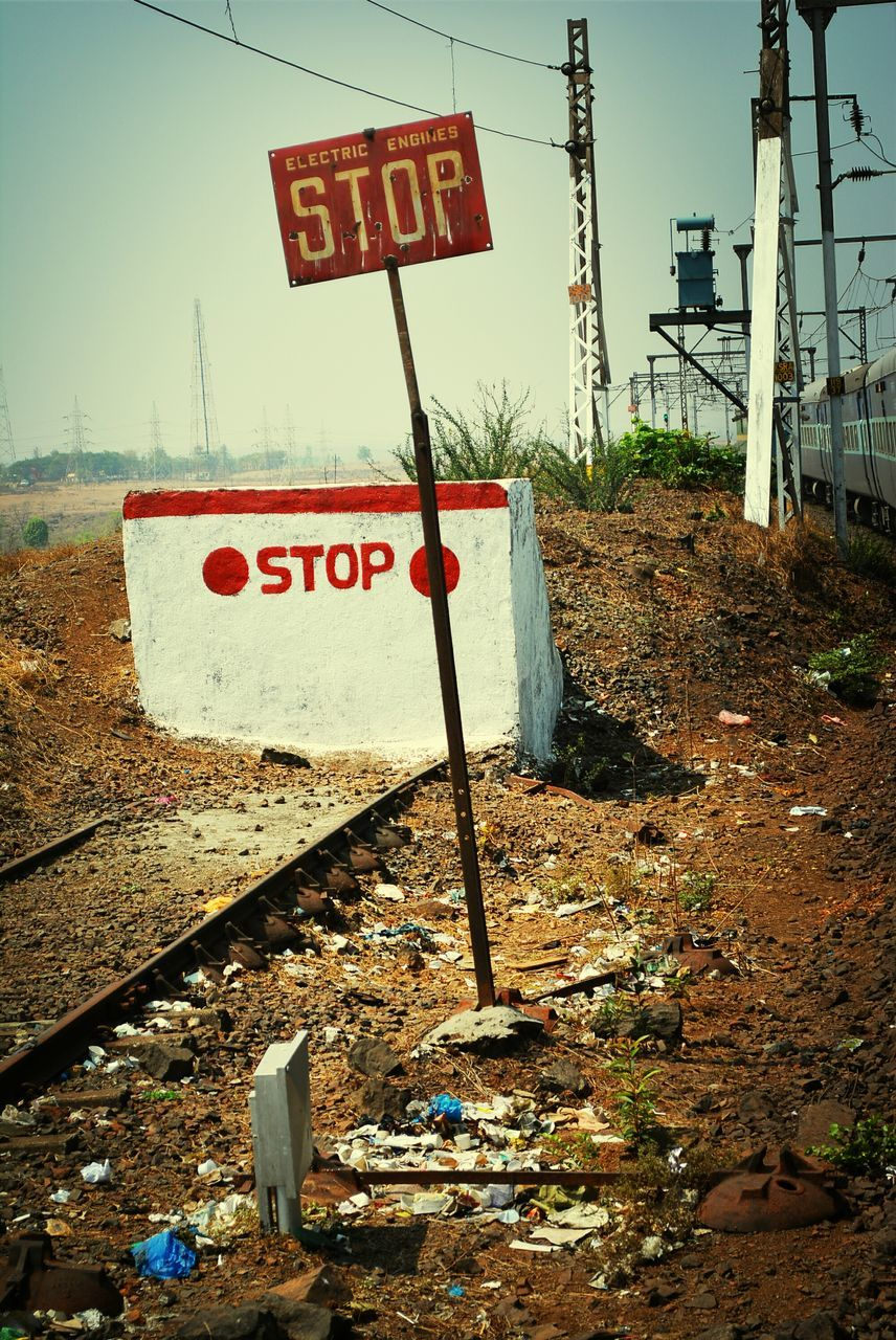 Stop Sign By Railroad Track On Sunny Day
