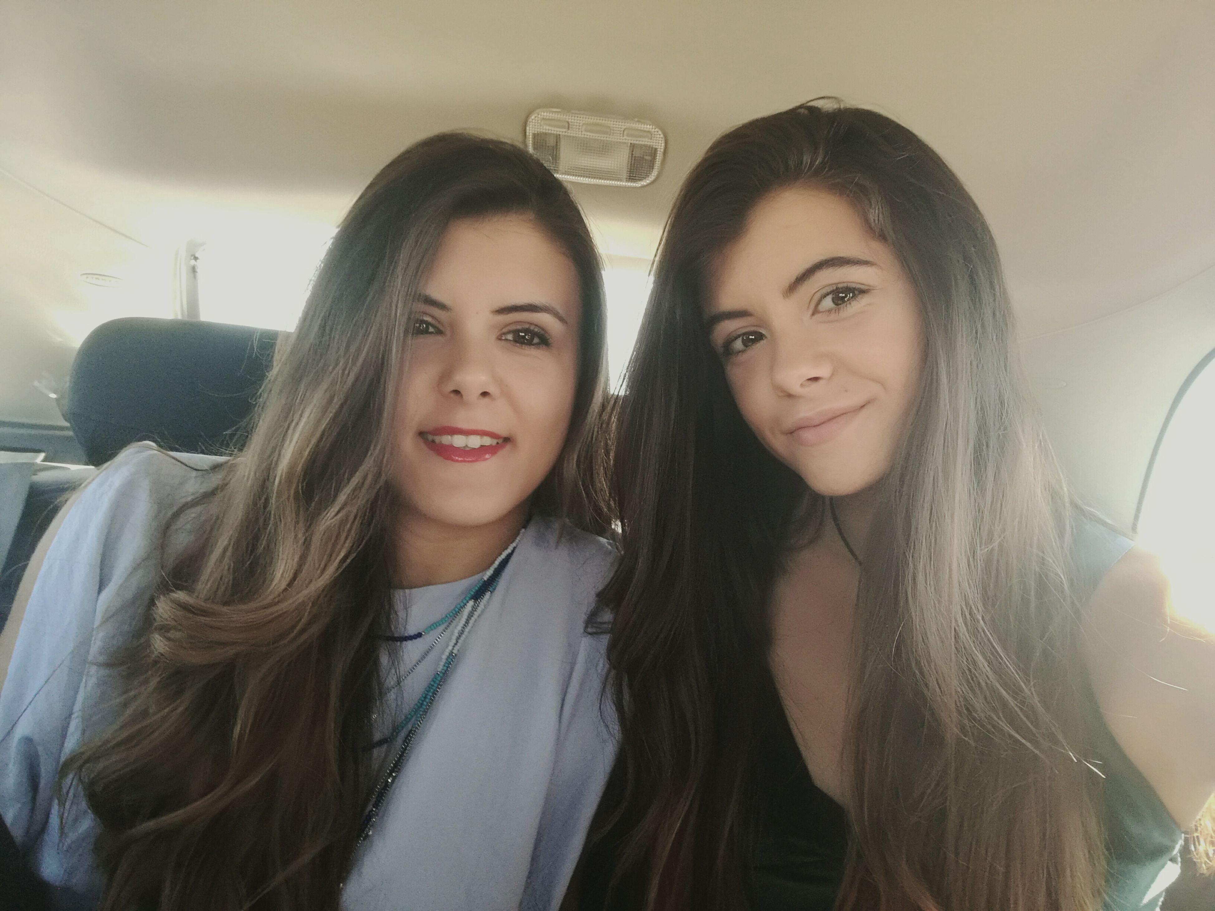 smiling, looking at camera, happiness, young adult, two people, transportation, young women, real people, portrait, long hair, front view, friendship, togetherness, indoors, close-up, day
