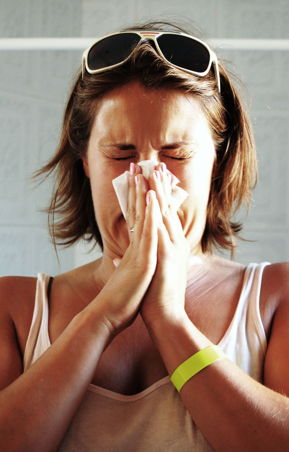 Woman blowing her nose hard into a tissue at home At Home Casual Clothing Coughing Female Glasses Health Home Long Hair Person Protection Sneeze Sneezing Sunglasses Tissue Woman Young Adult Young Women