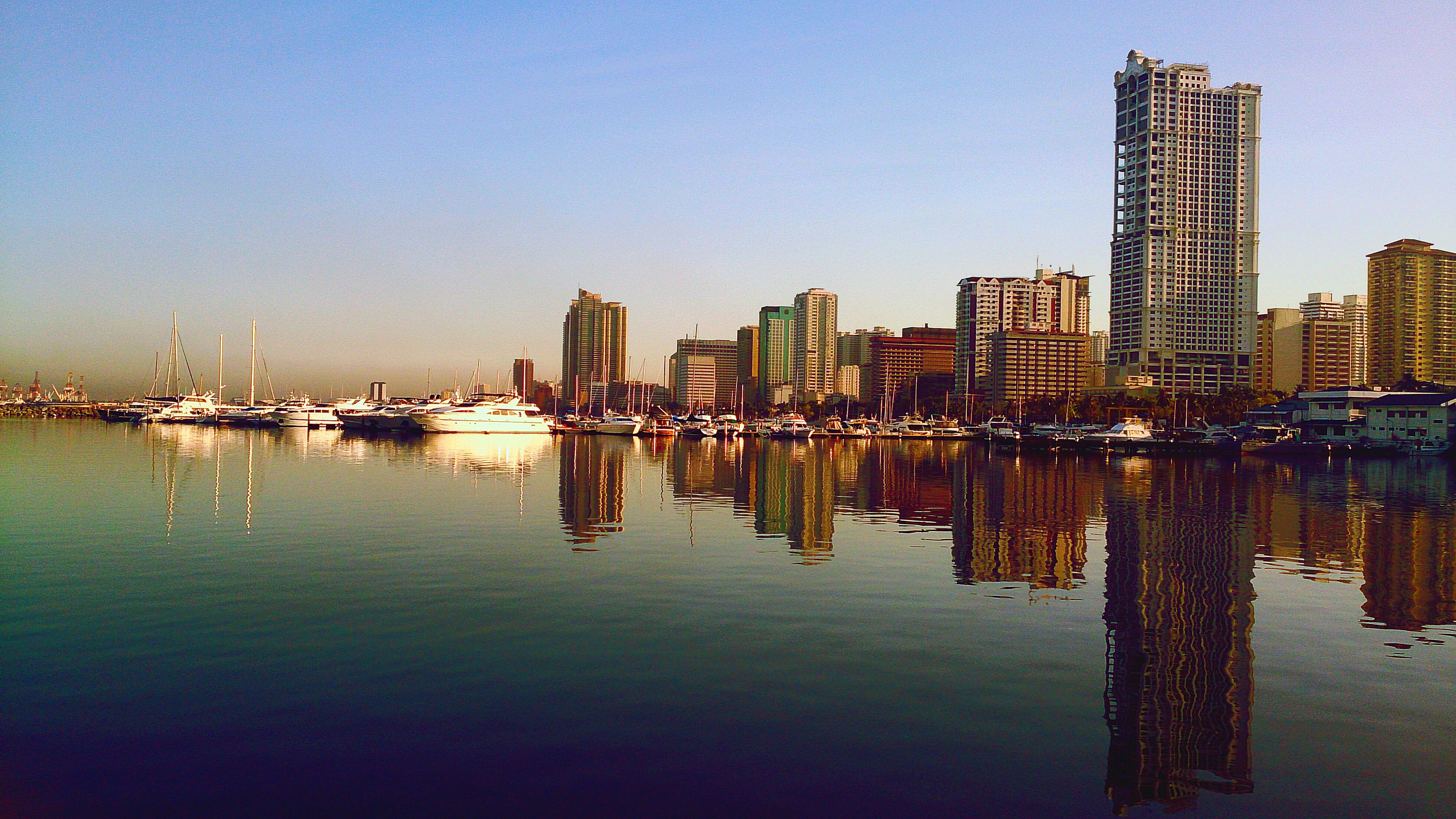 building exterior, architecture, water, city, built structure, reflection, clear sky, waterfront, skyscraper, cityscape, illuminated, copy space, river, urban skyline, tall - high, tower, blue, skyline, modern, tall