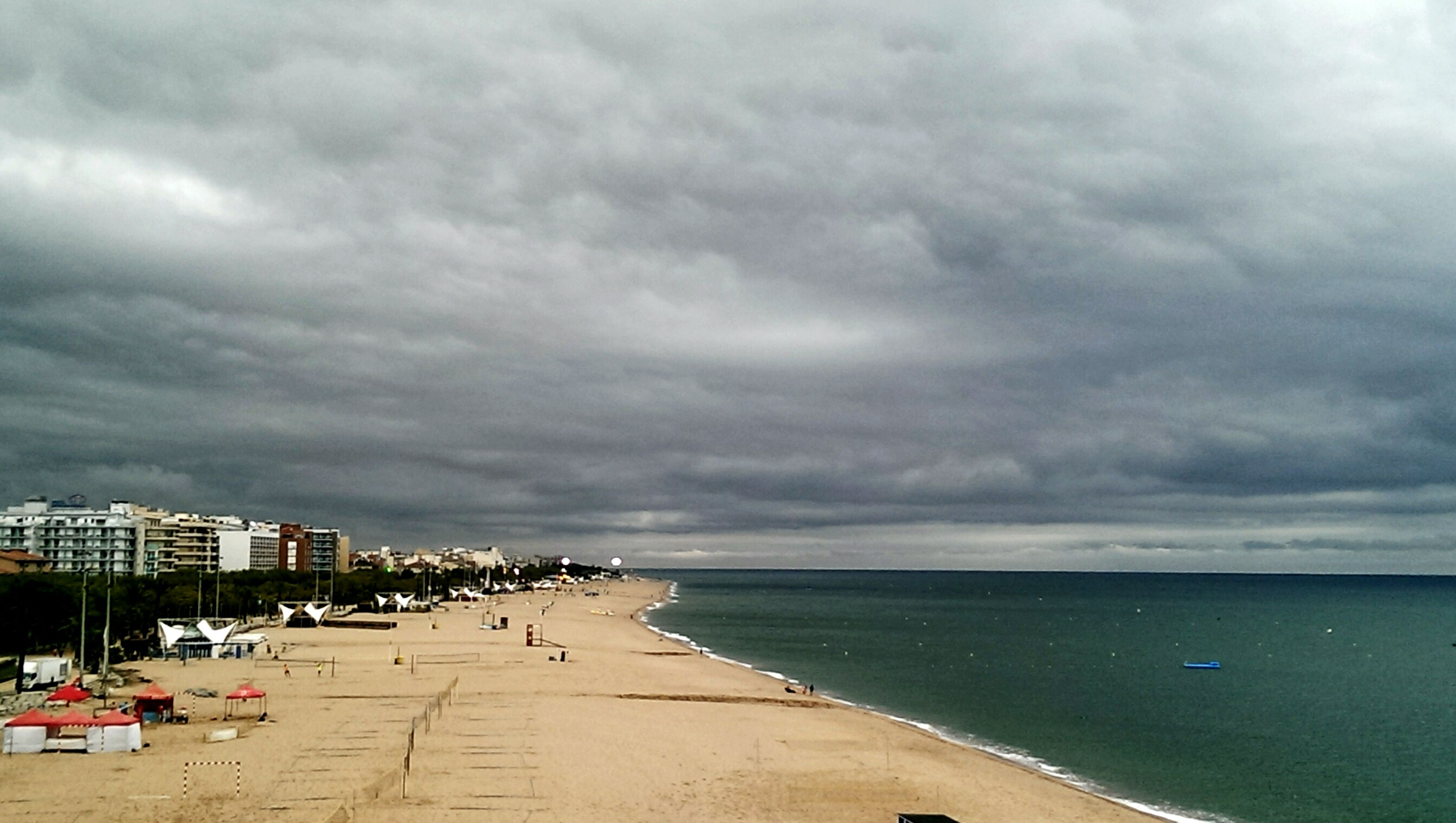 sky, sea, cloud - sky, water, beach, cloudy, horizon over water, building exterior, built structure, architecture, cloud, shore, incidental people, overcast, nature, weather, sand, outdoors, scenics, day