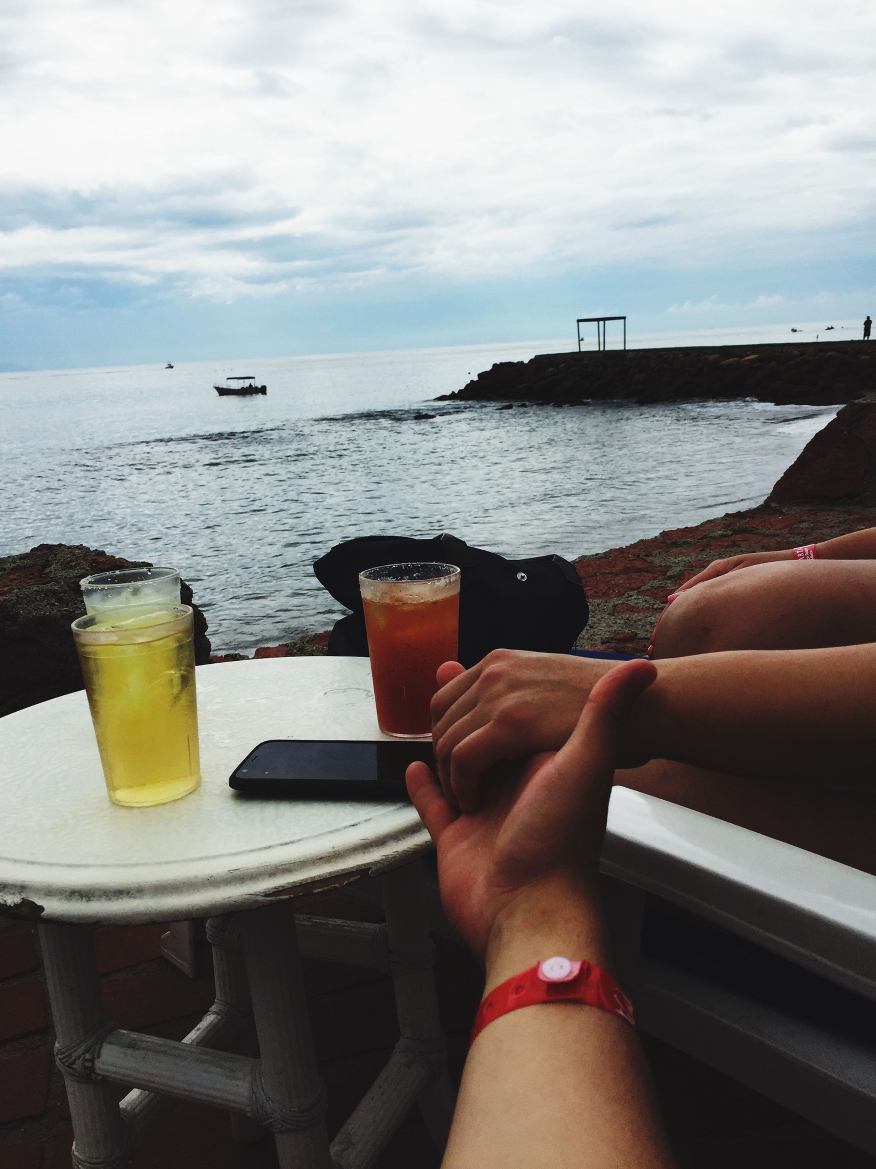 sea, drink, personal perspective, water, refreshment, food and drink, part of, horizon over water, lifestyles, sky, person, leisure activity, cropped, beach, holding, low section