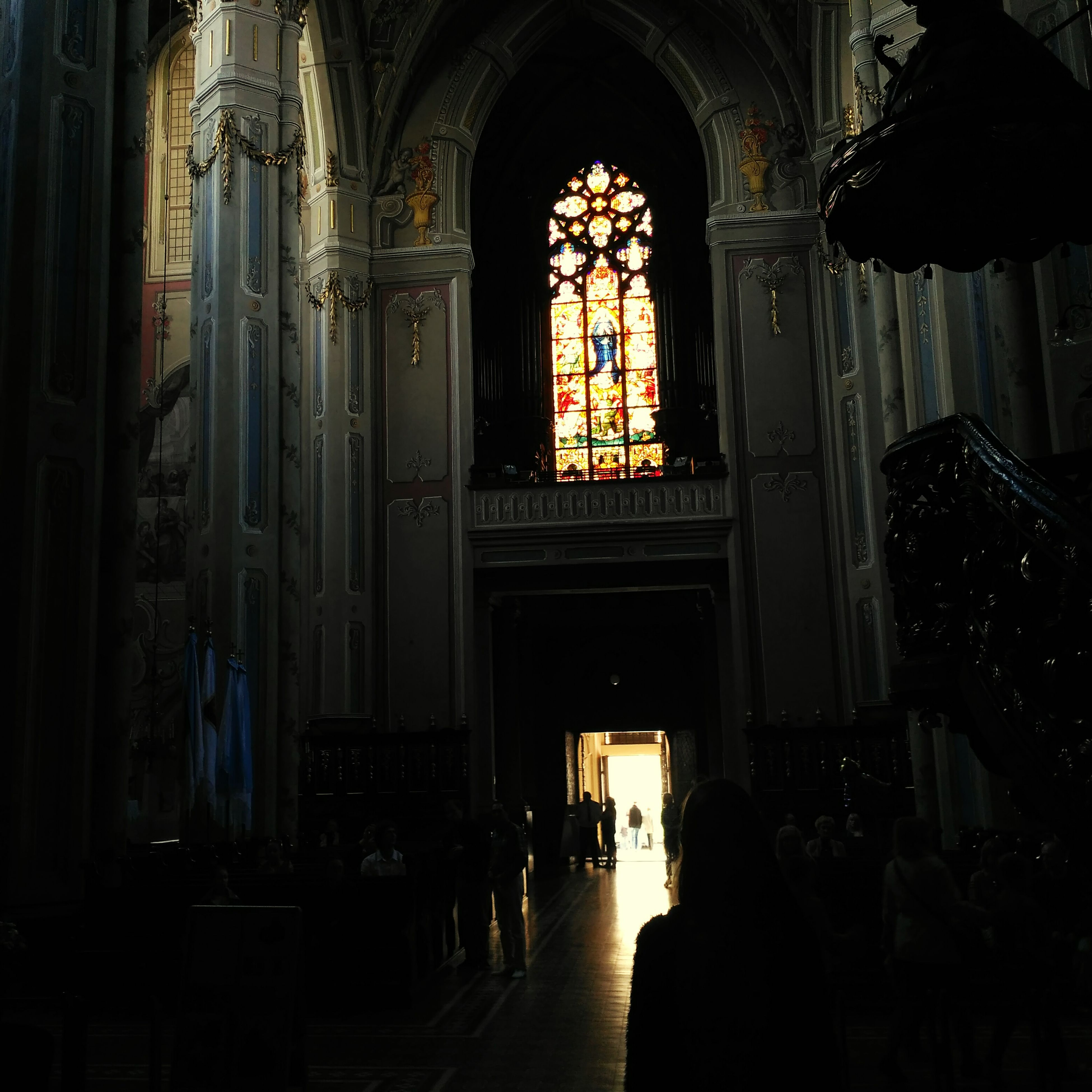 indoors, place of worship, religion, church, spirituality, architecture, built structure, arch, window, cathedral, illuminated, interior, curtain, dark, stained glass, no people, history, lighting equipment