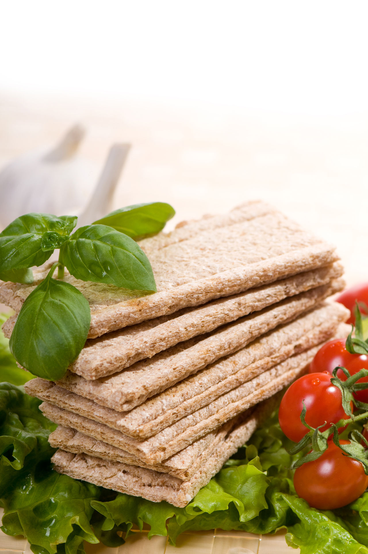 Stack of dry crisp bread slices with cherry tomato and basil green leaves on wooden mat, food staple of diet products in horizontal orientation, nobody. Bread Cereal Cracker Crackers Crisp Crispbread  Crisps Crispy Crunchy Diet Food Food And Drink Healthy Eating Knäckebröd No People Ocimum Ready-to-eat Slices Snack Snacks Tomato Vegetable Wafer Wasa Wholewheat