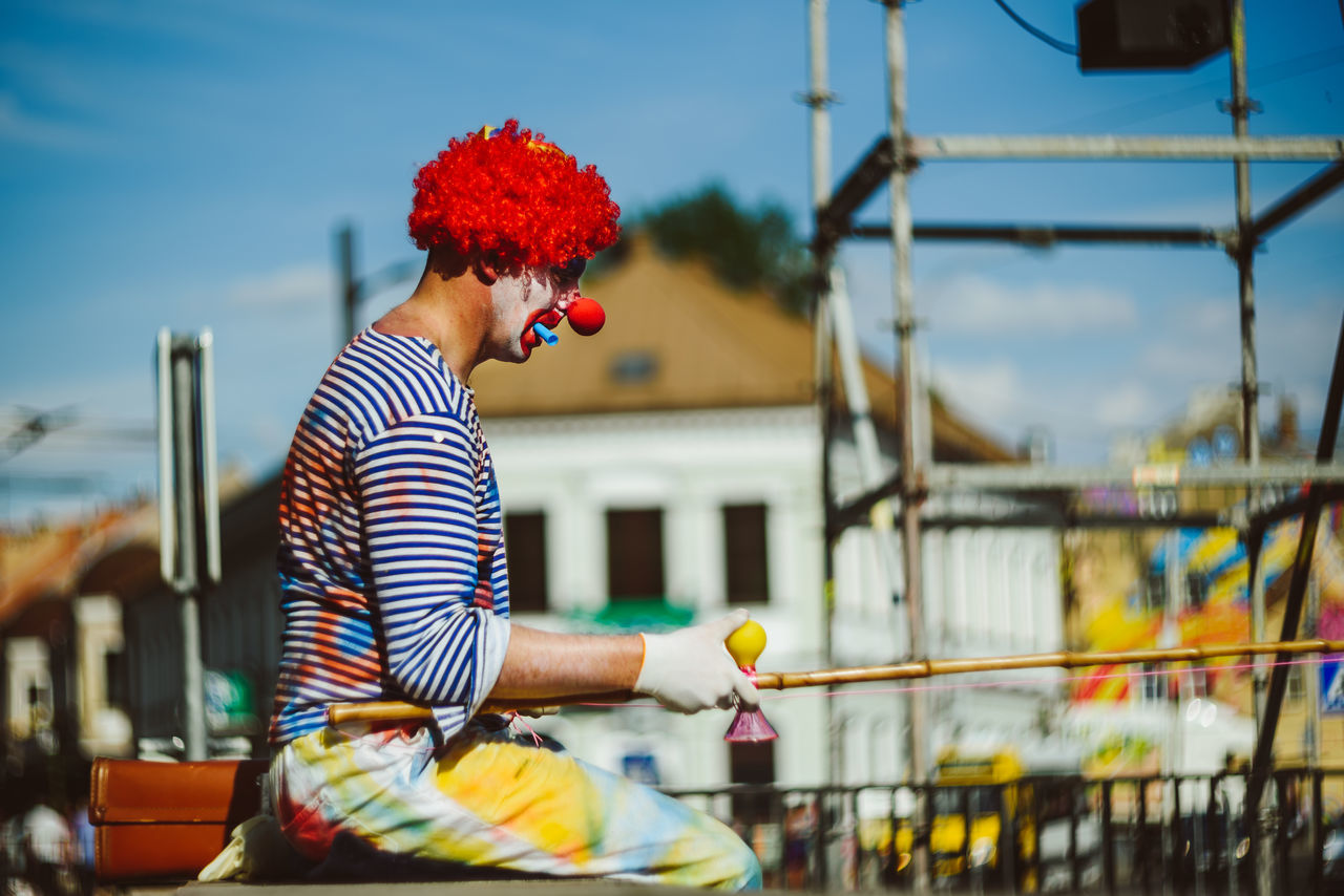 Clown Architecture Building Exterior Built Structure Casual Clothing Clown Day Festive Focus On Foreground Hanseatic City One Person Outdoors People Real People Sky Street Life Striped Young Adult Young Women